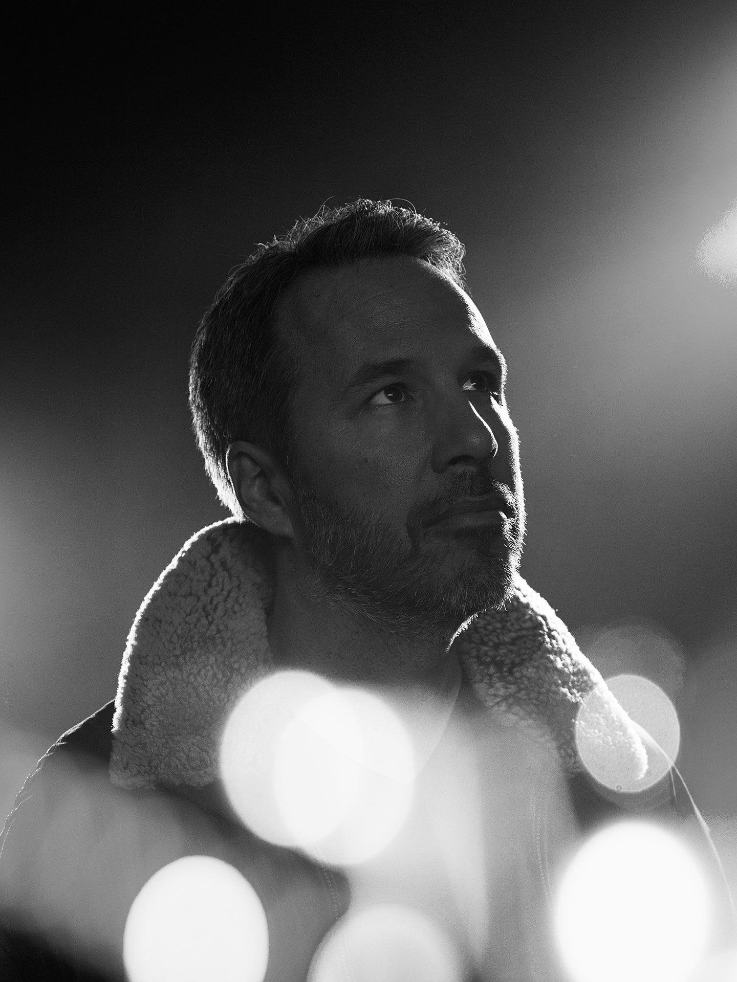 Black and white portrait of Denis Villeneuve with light spots.