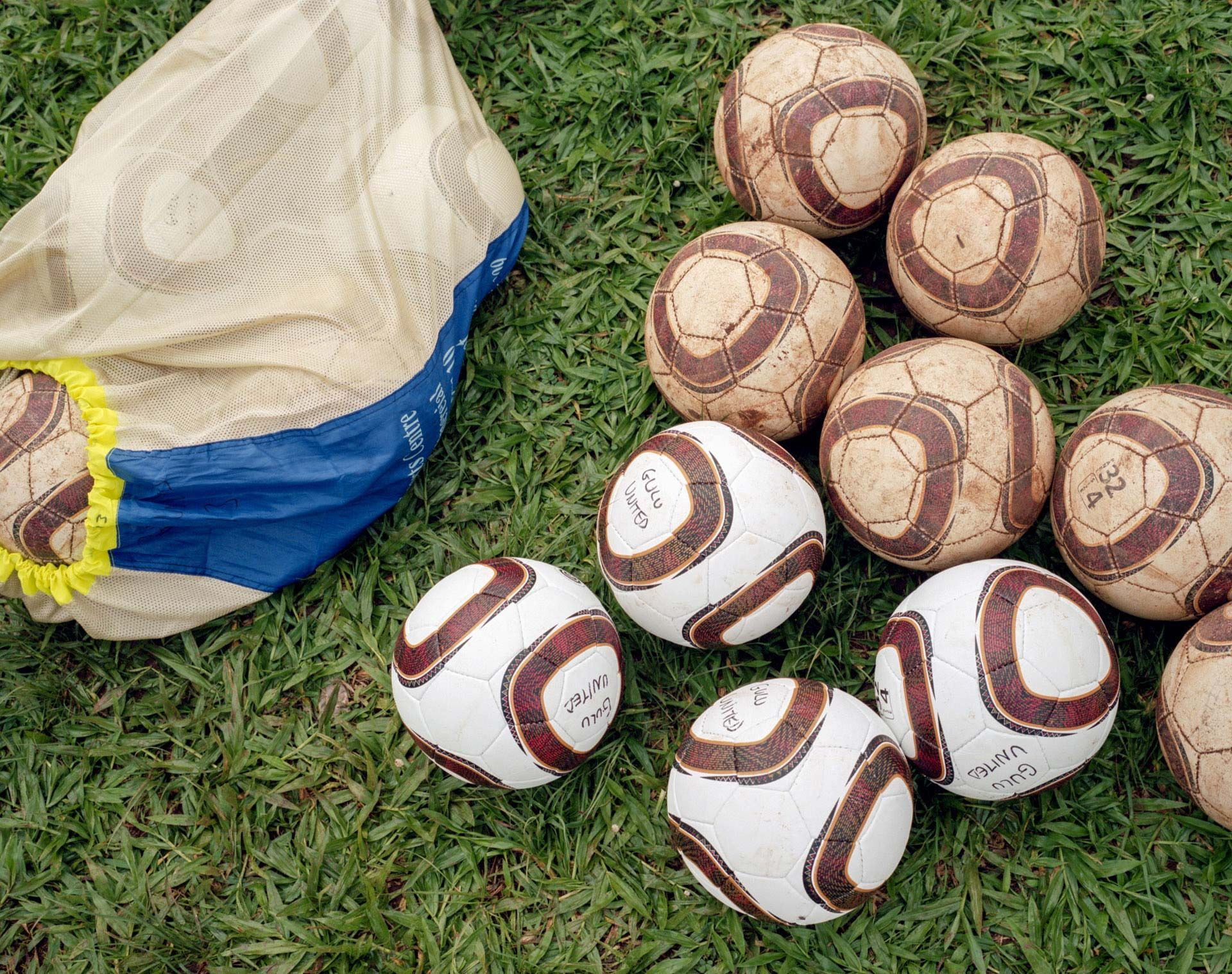 picture of tattered and new soccer balls side by side on the ground by Alexi Hobbs in Uganda for Football for Good with Sportsnet