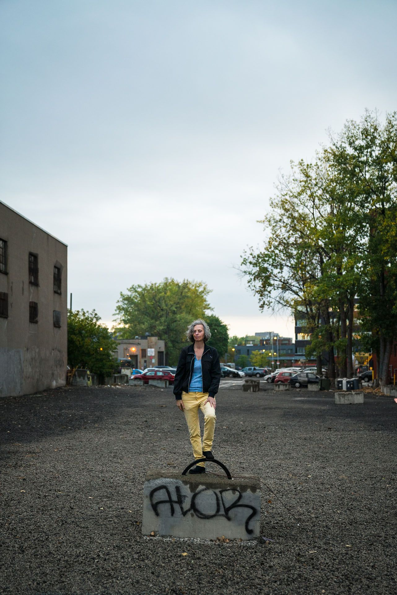 grey haired woman posing on concrete block in empty parking lot by Bruno Florin for mile ex mille vie