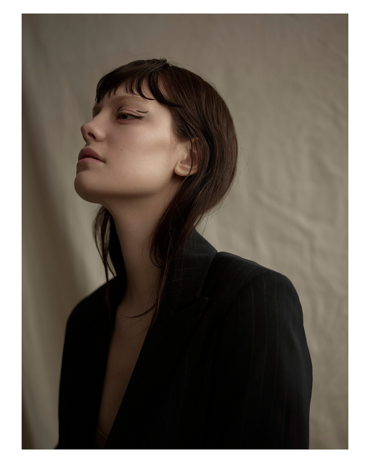 woman model wearing black and light stripped suit jacket looking away head high on blurred beige fabric background by Maxyme G Delisle for Mariane