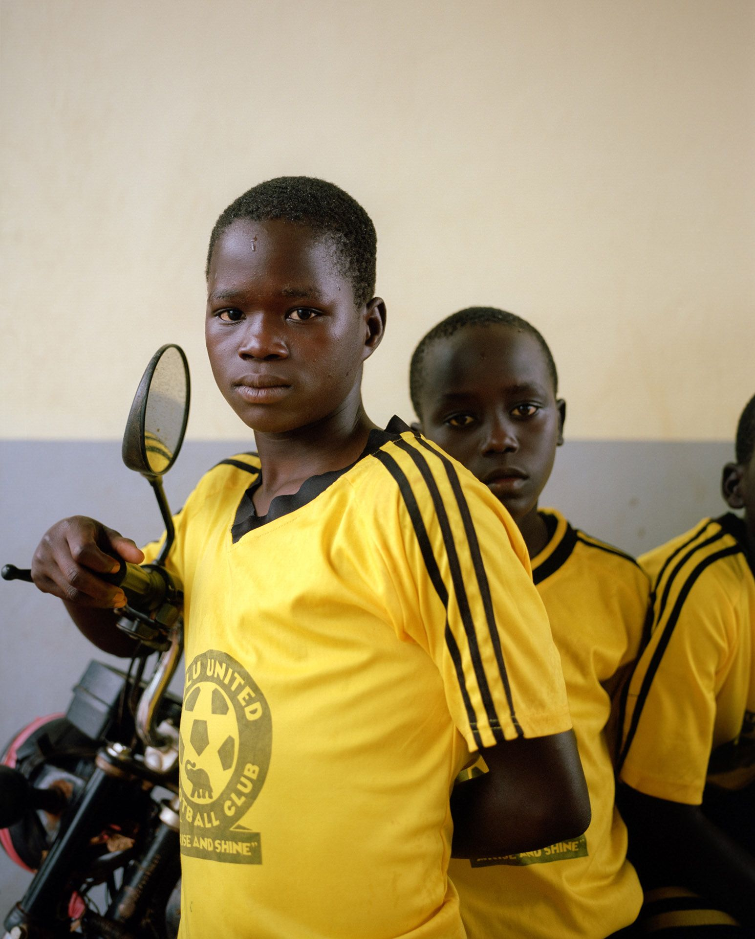 close up of young black boys on scooter looking at camera by Alexi Hobbs in Uganda for Football for good with Sportsnet