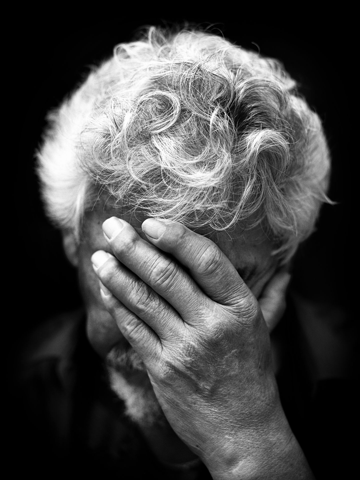 Black and white portrait of David Suzuki with his forehead on his hand.