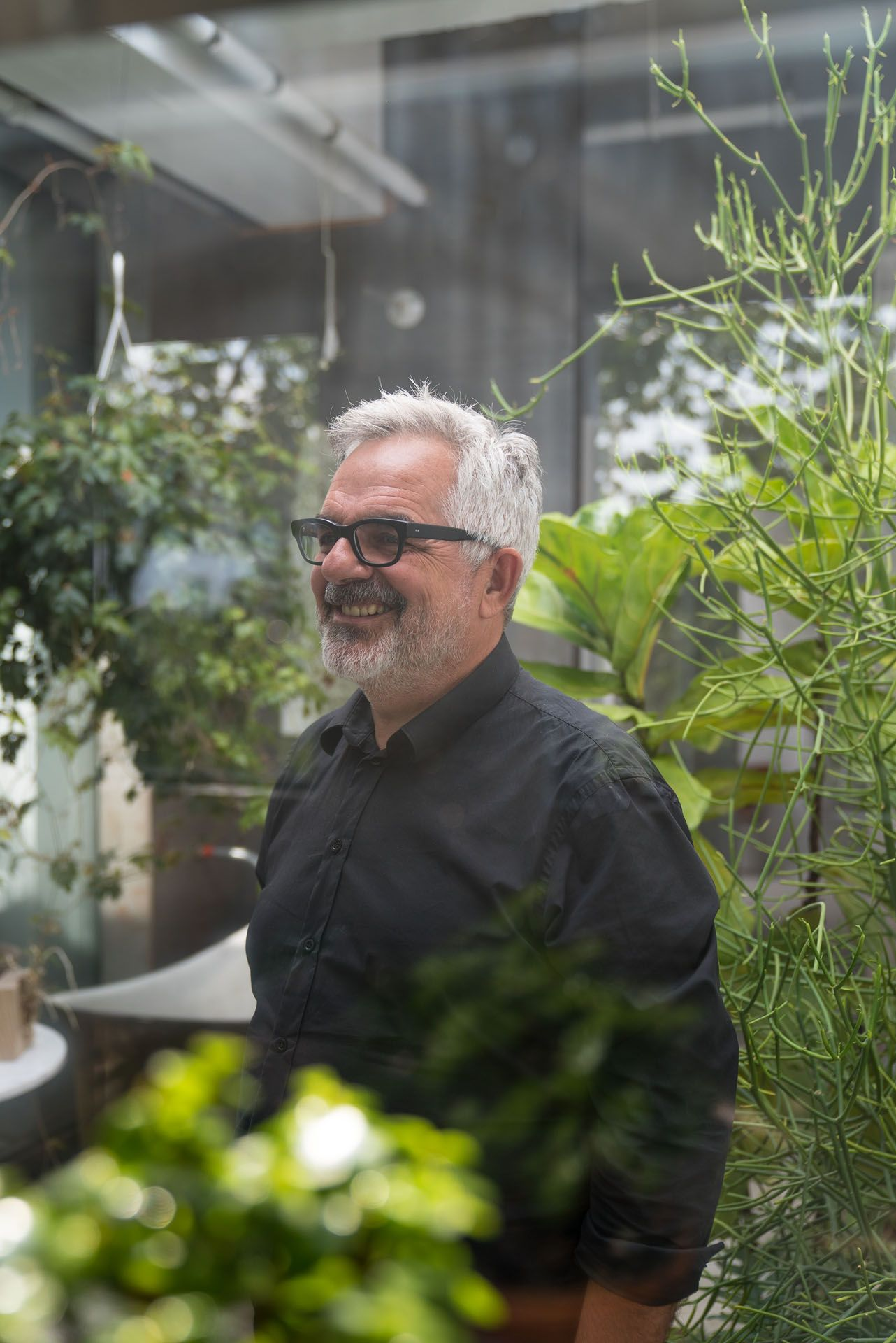 white haired man wearing glasses and black shirt posing inside greenhouse among plants by Bruno Florin for mile ex mille vie