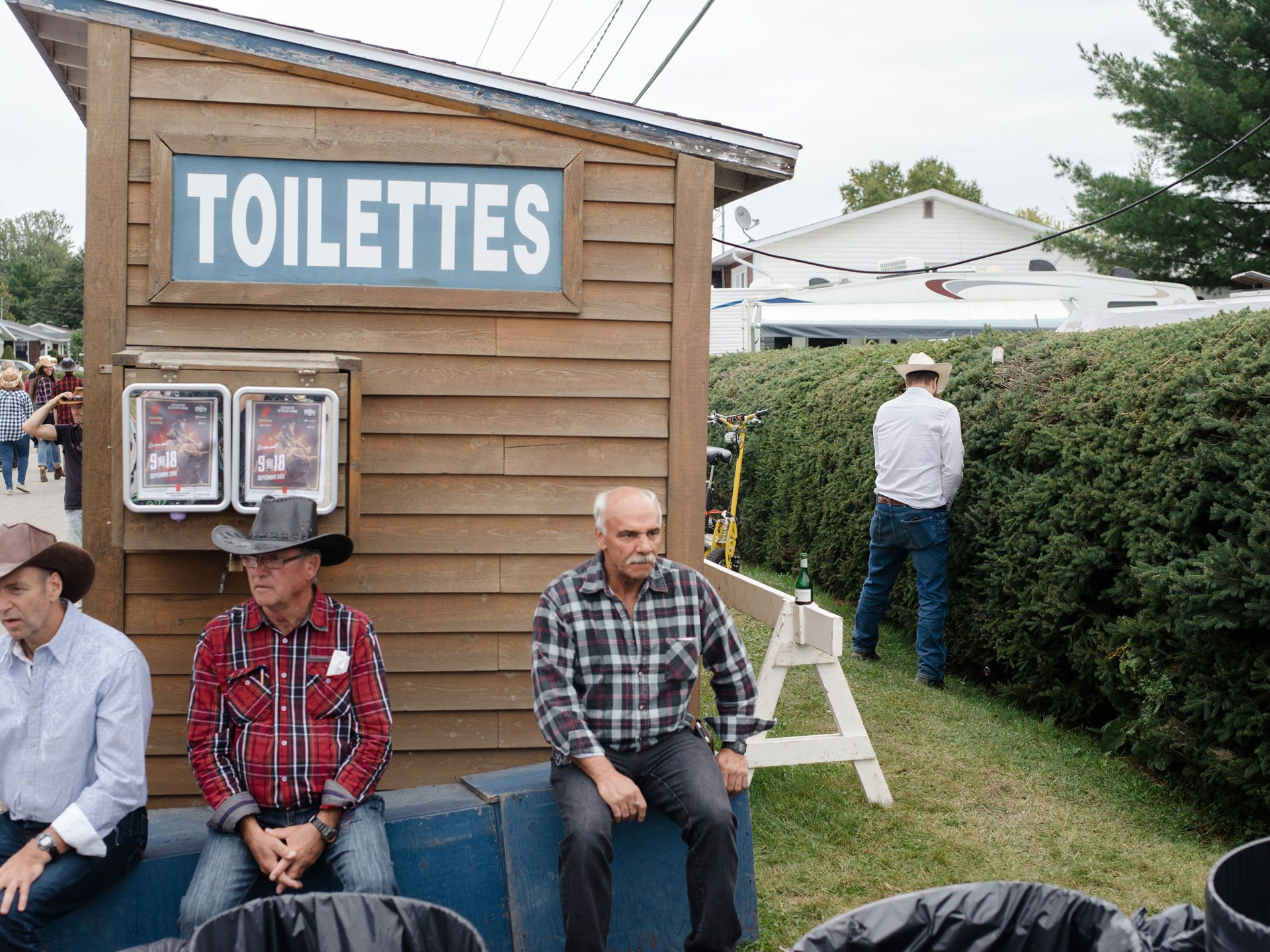 toilet shack with man peeing in the bushes next to it by Alexi Hobbs for Larose Paris in St-Tite