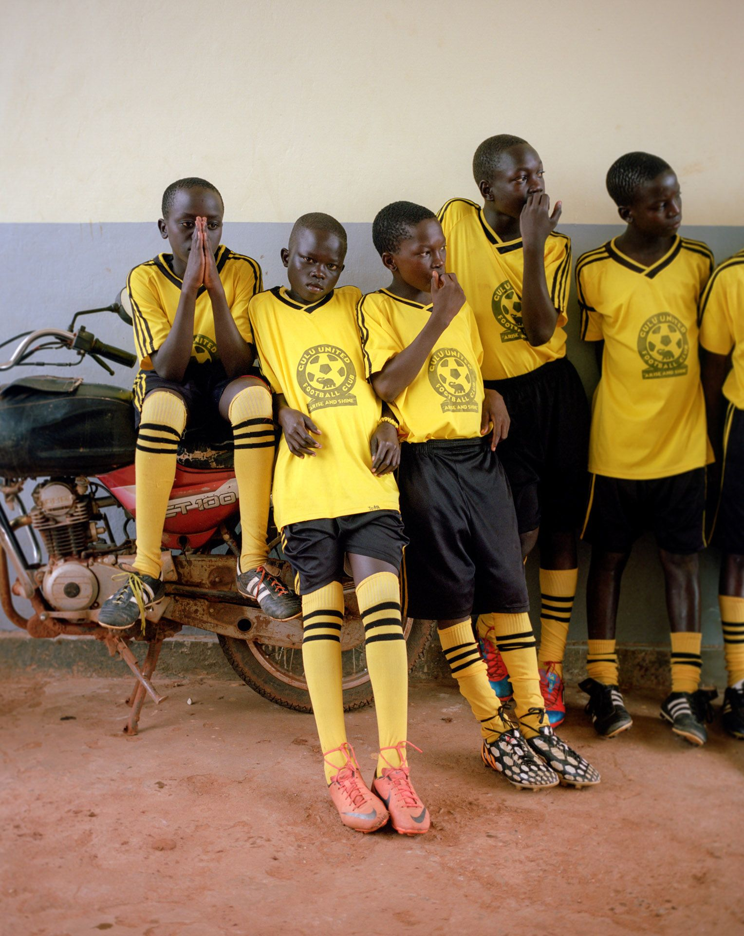 young black boys soccer players waiting on parked scooter by Alexi Hobbs in Uganda for Football for good with Sportsnet