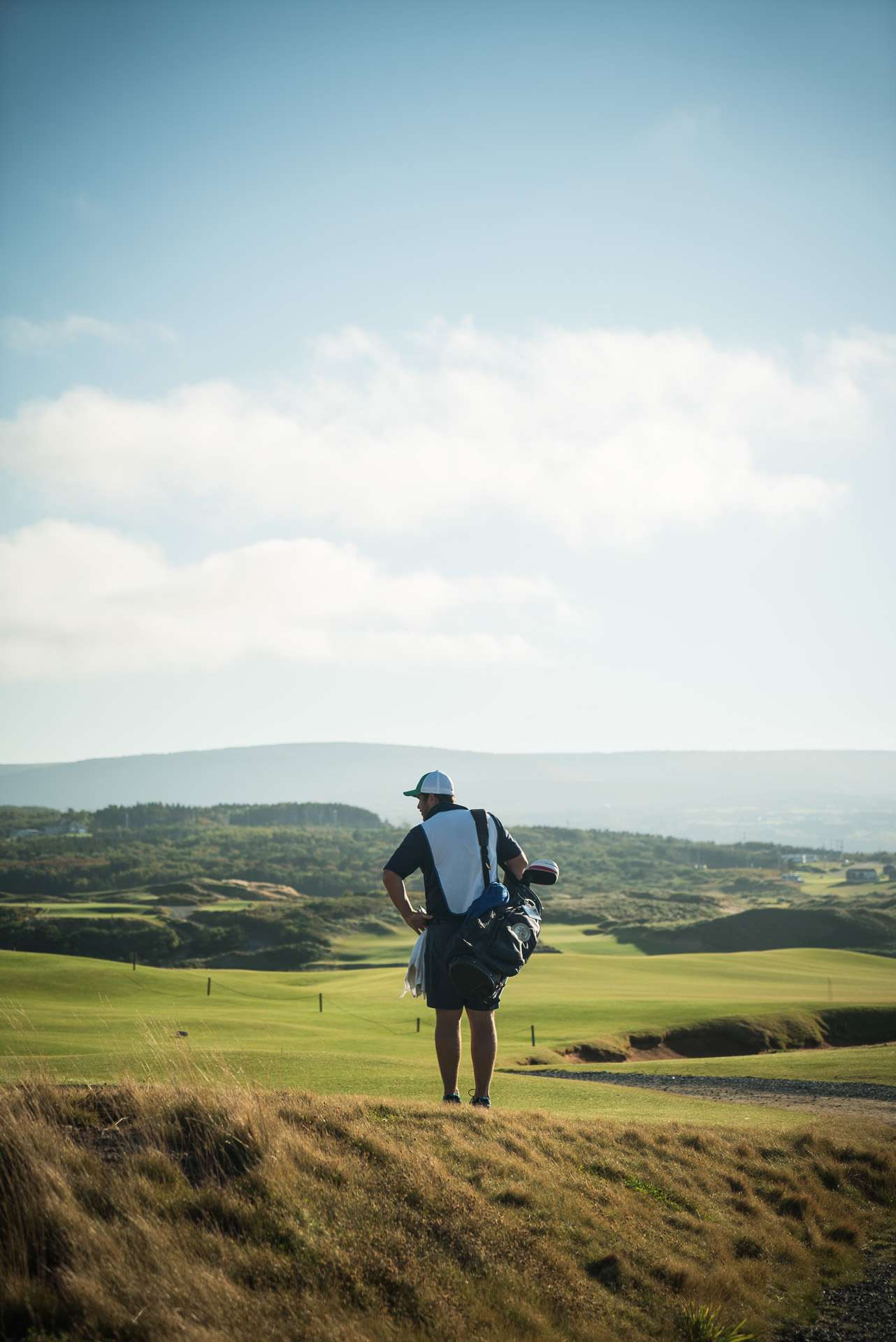 golfer hands on hips looking at the course with bag of clubs on shoulder by Bruno Florin for Mercedes Magazine