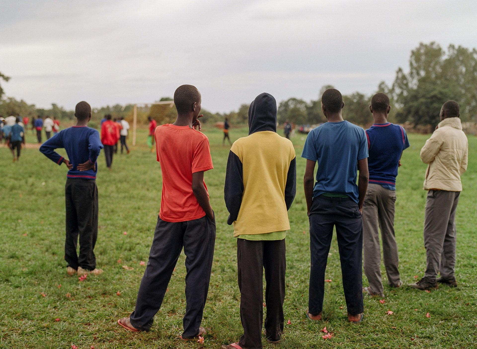 group of boys watching soccer match from the sidelines by Alexi Hobbs in Uganda for Football for good with Sportsnet