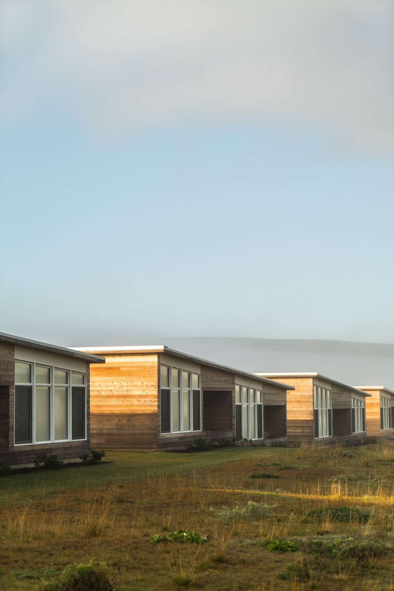 row of wooden bungalows in gold light by Bruno Florin for Mercedes Magazine