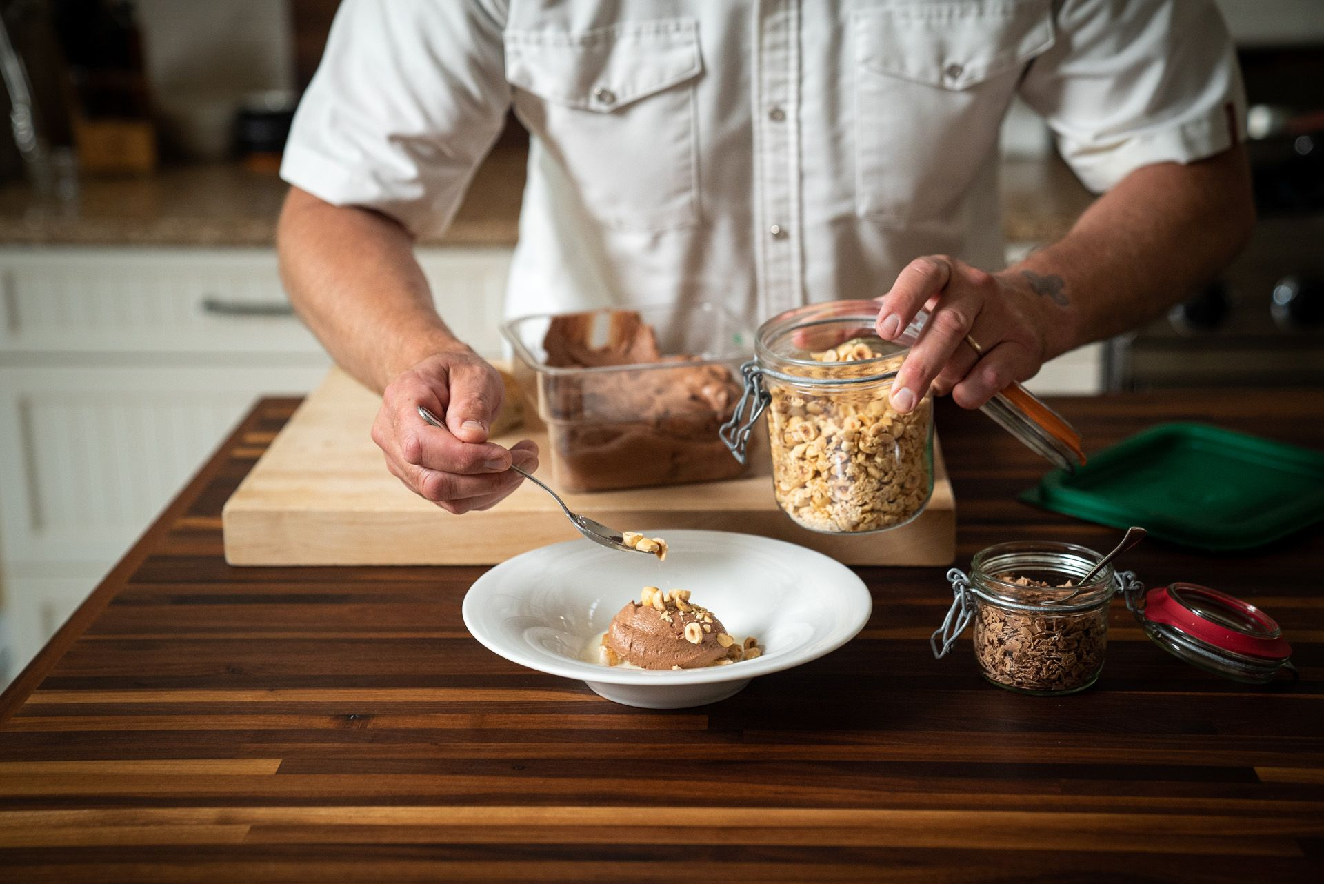 chef Michael Allemeier topping bowl of coffee mousse with roasted hazelnuts by Bruno Florin for Van Houtte 100th anniversary
