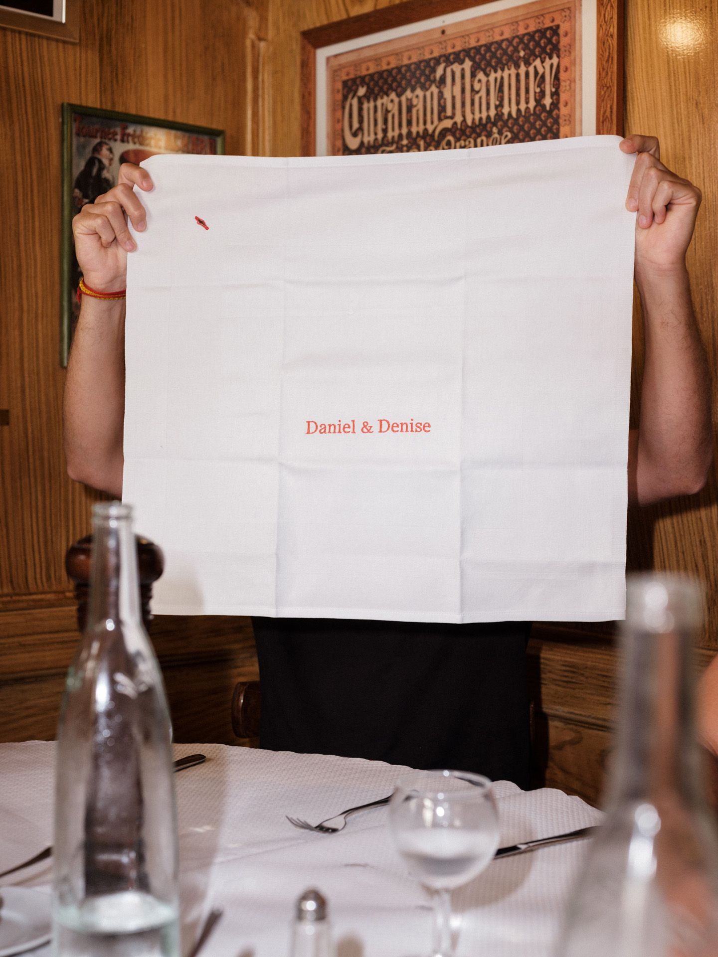 man holding up a white fabric napkin with 'Daniel & Denise' embroidered in red by Alexi Hobbs in Auvergne for Reflets de France
