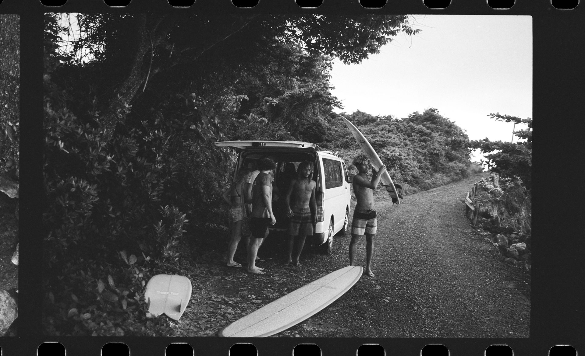 group of young jamaicans getting out of van getting their surfboards next to the sea by Oumayma B Tanfous in Jamaica