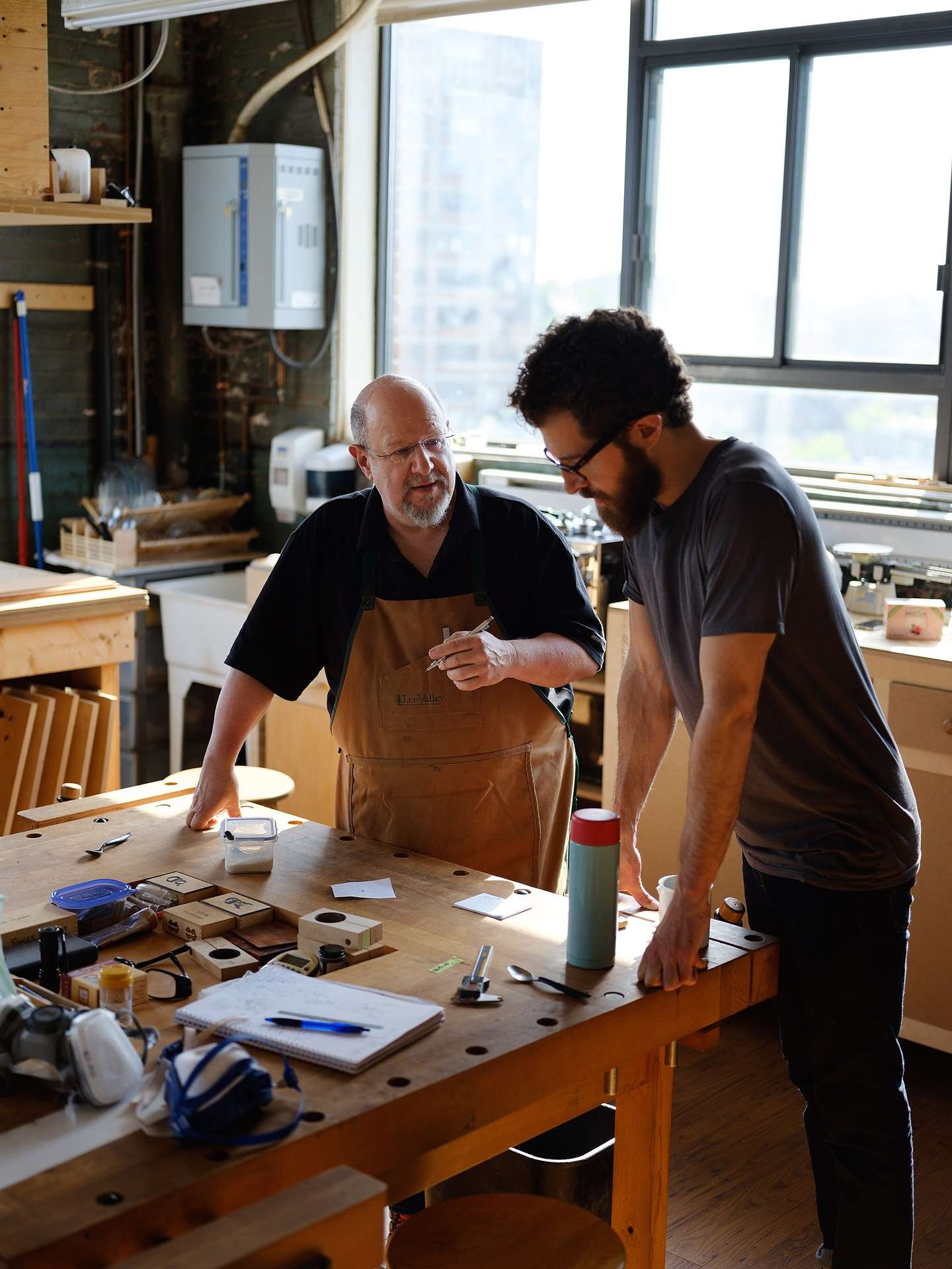 two men in guitar making shop over a table by Guillaume Simoneau for Mercedes Benz Magazine