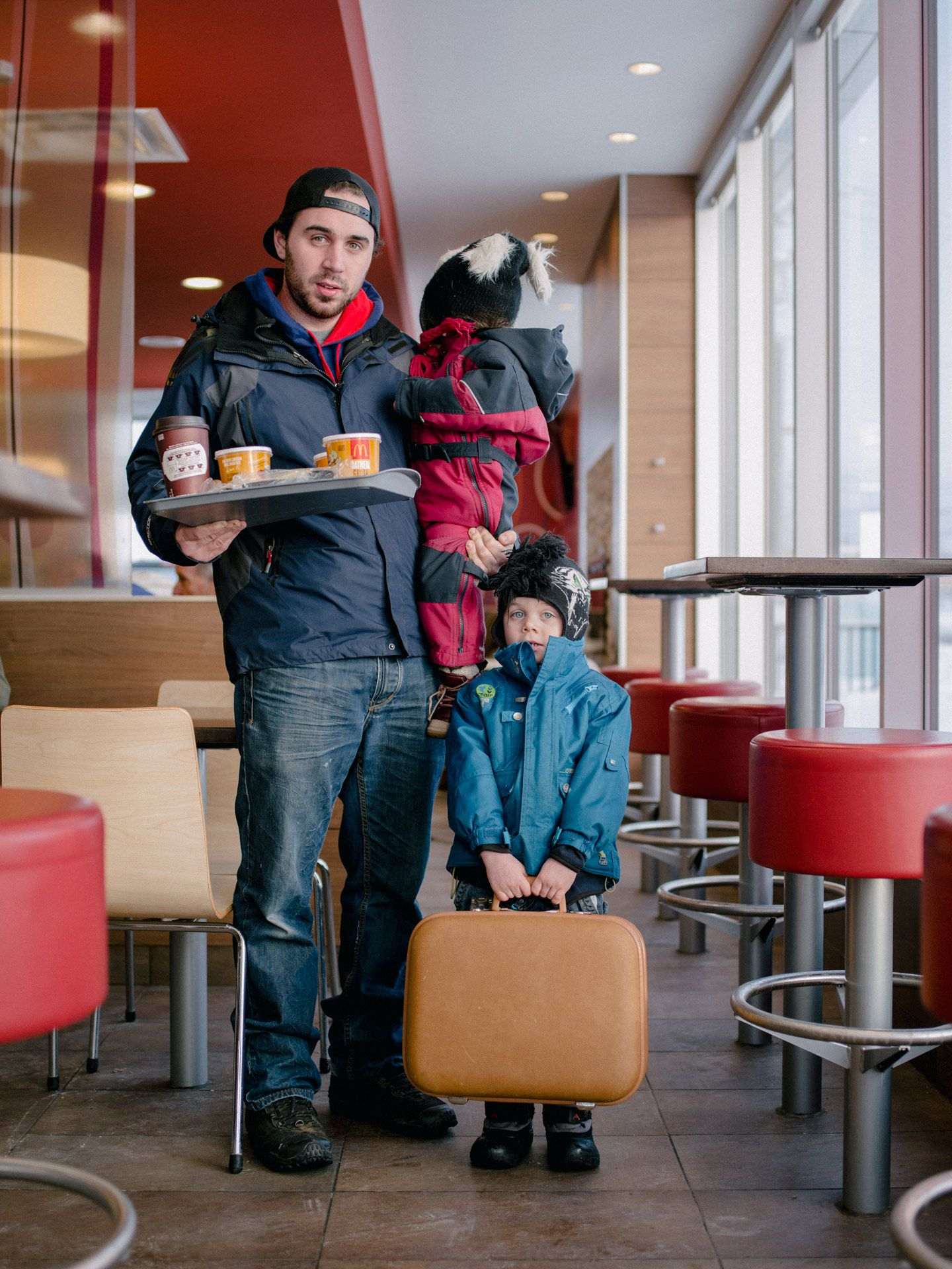 father with his two children holding one in his arm and a tray with food the other kid on the ground holding a suitcase by Alexi Hobbs for McDonald's