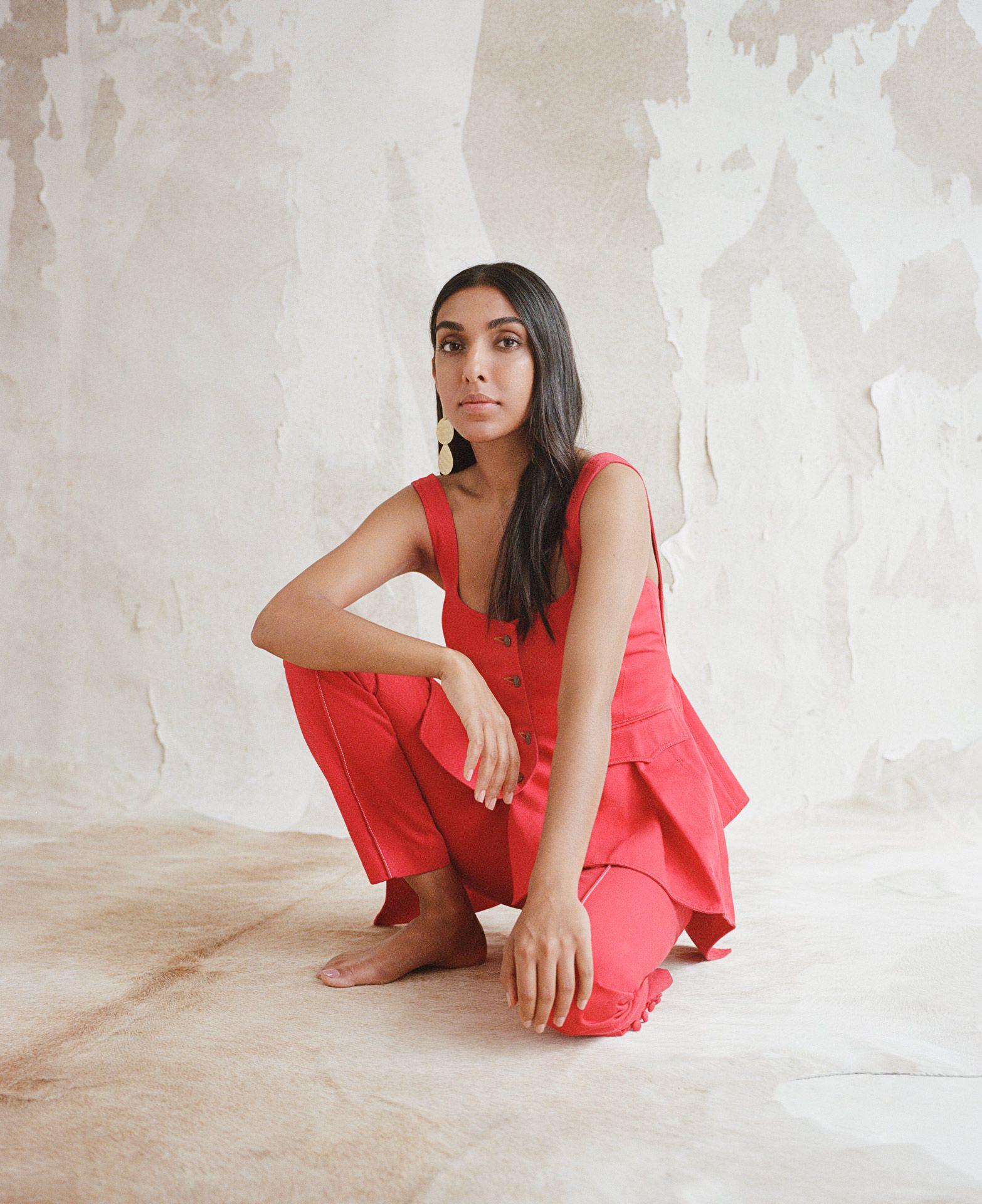 writer Rupi Kaur wearing red ensemble looking at camera by Oumayma B Tanfous for Vogue Espana