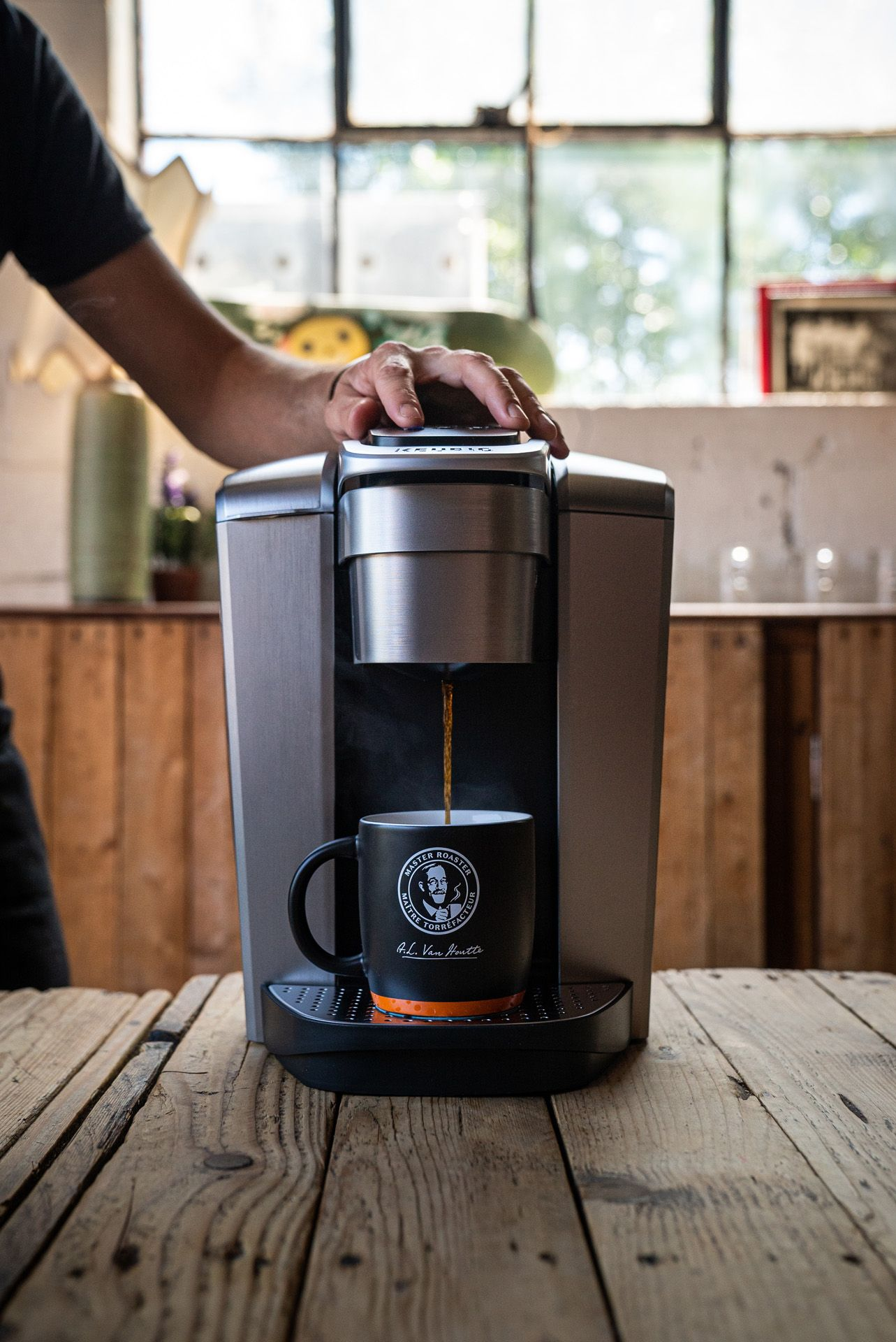 chef Sebastian Harrisson-Cloutier making a coffee with a Keurig machine in a Van Houtte branded cup by Bruno Florin for Van Houtte 100th anniversary