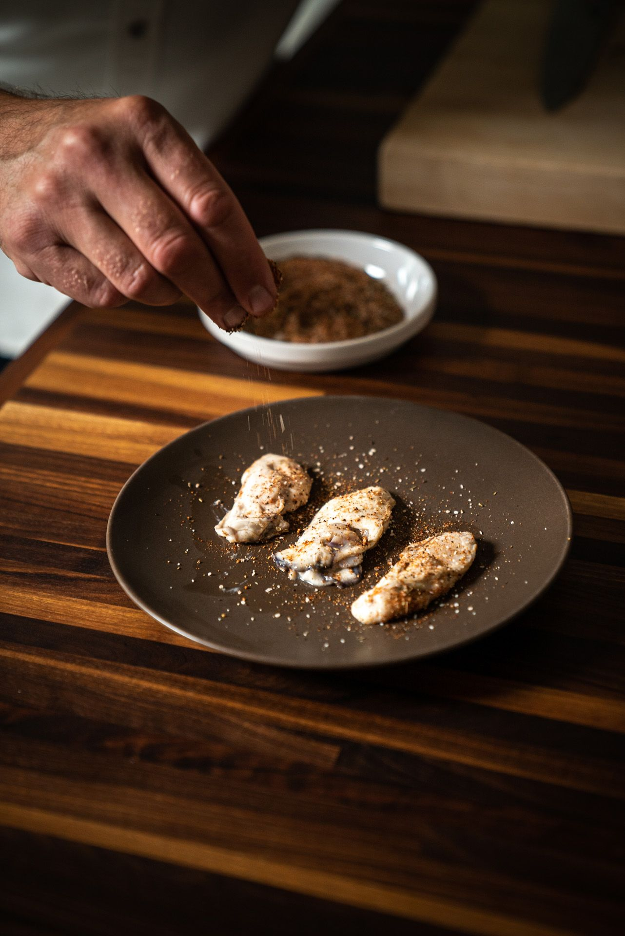chef Michael Allemeier sprinkling spices over chicken wings by Bruno Florin for Van Houtte 100th anniversary