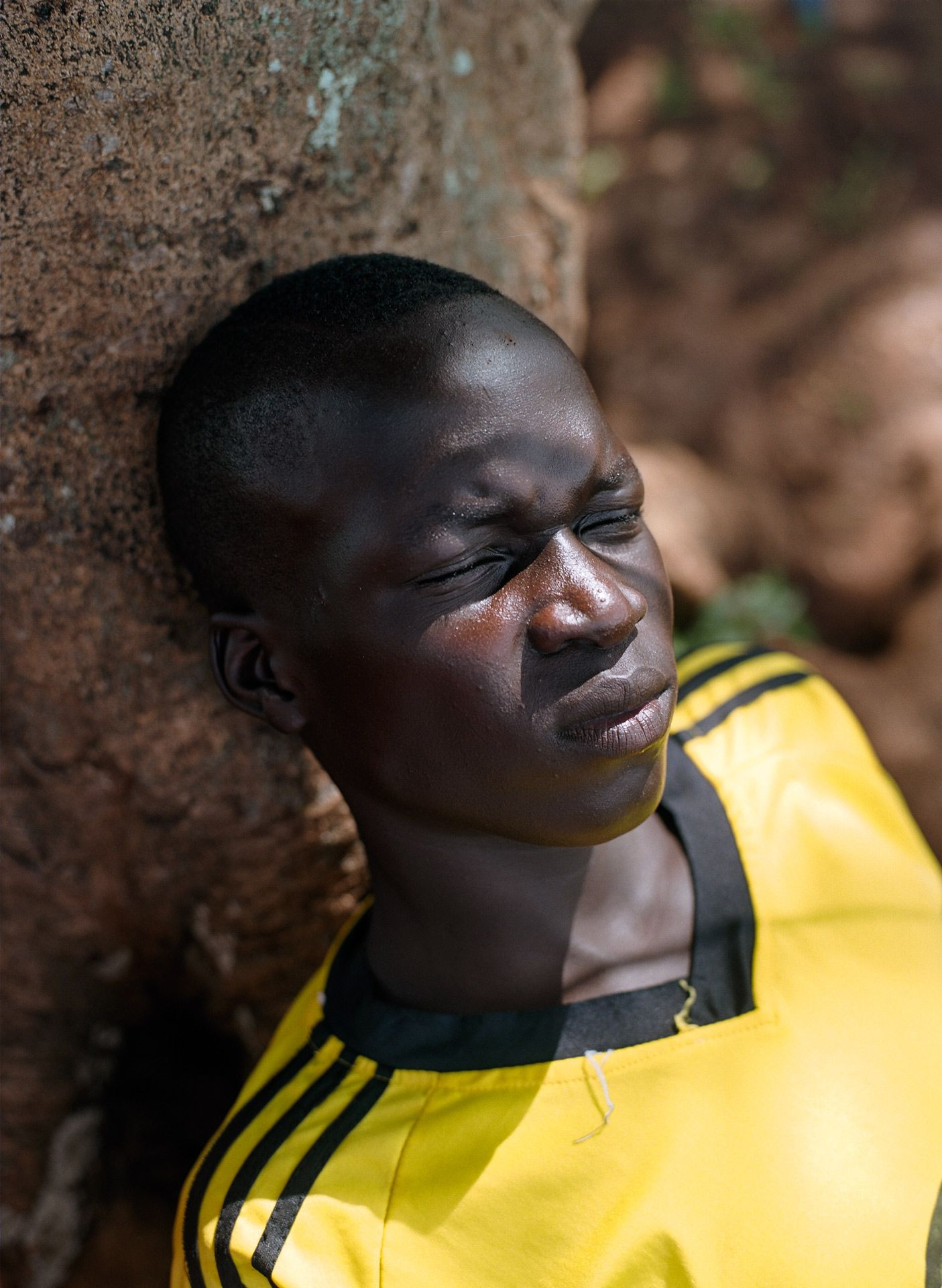 young black boy resting in the shade frowning with eyes closed against a tree by Alexi Hobbs in Uganda for Football for good with Sportsnet