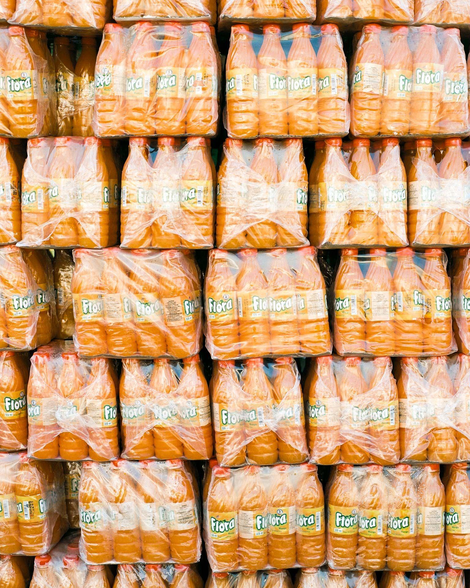 stack of orange bottled drinks named Flora by Alexi Hobbs in Uganda for Football for Good with Sportsnet