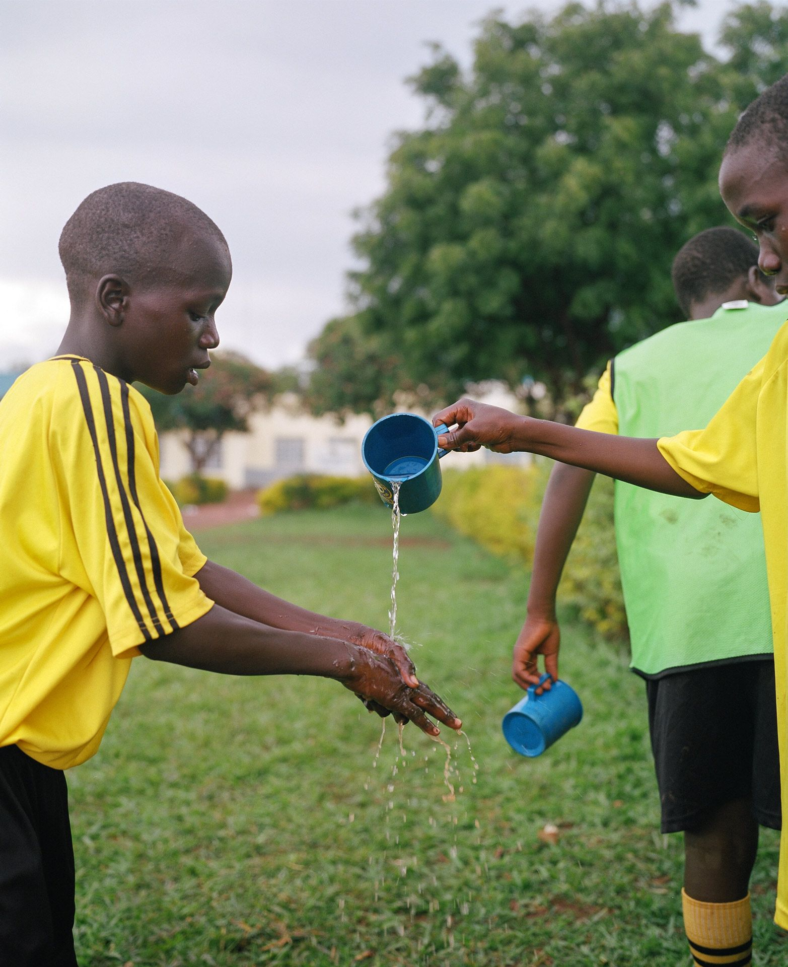 young black boy slowly pouring a blue cup of water for another boy to wash his hands by Alexi Hobbs in Uganda for Football for Good with Sportsnet
