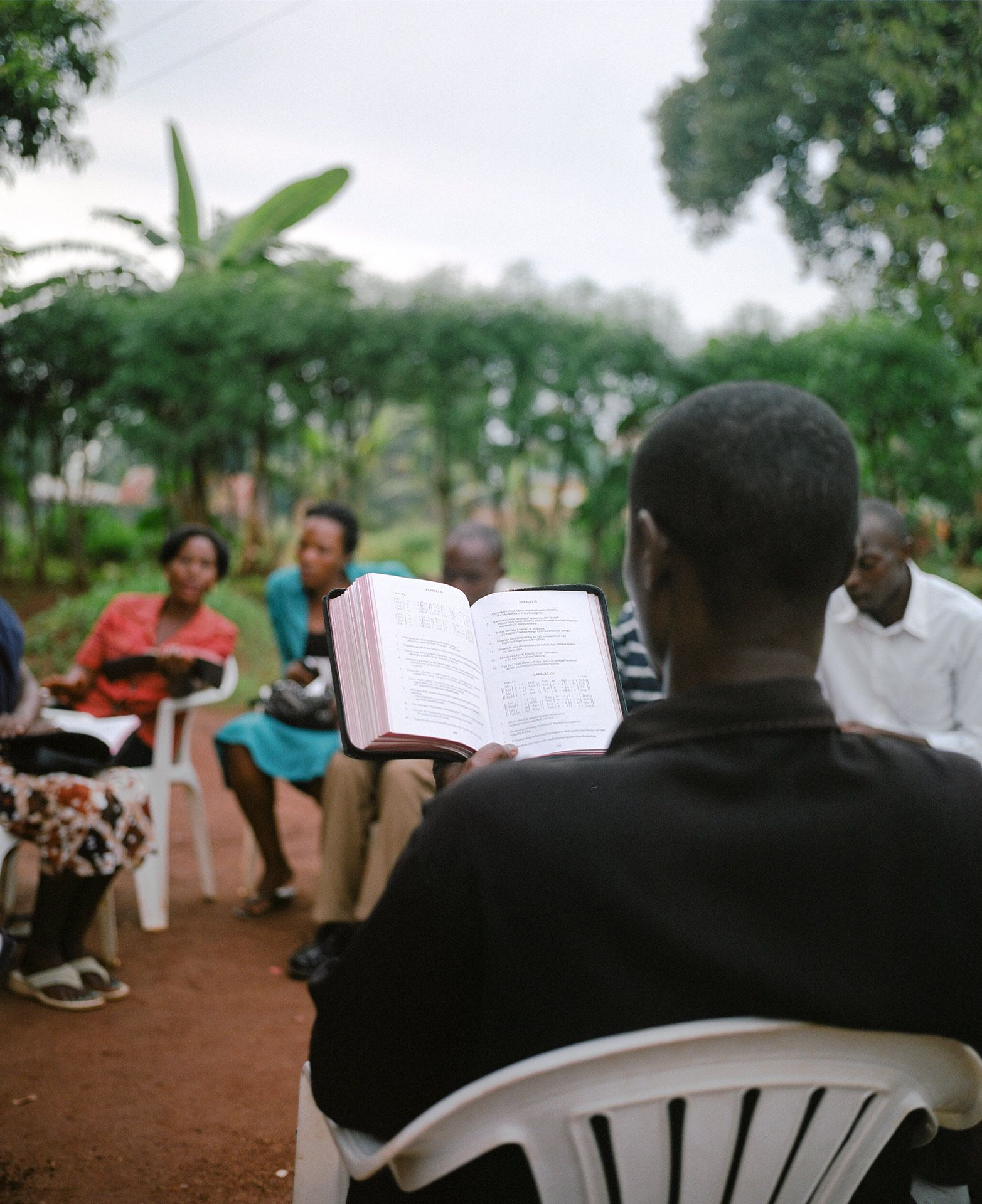 black man sitting on white plastic chair reading the bible with other people by Alexi Hobbs in Uganda for Football for Good with Sportsnet