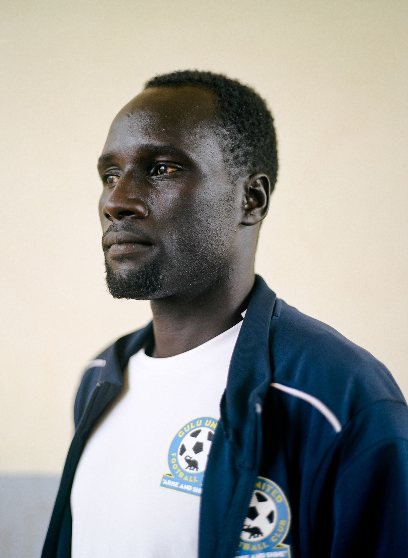 portrait of black man looking away dressed as coach of team by Alexi Hobbs in Uganda for Football for Good with Sportsnet