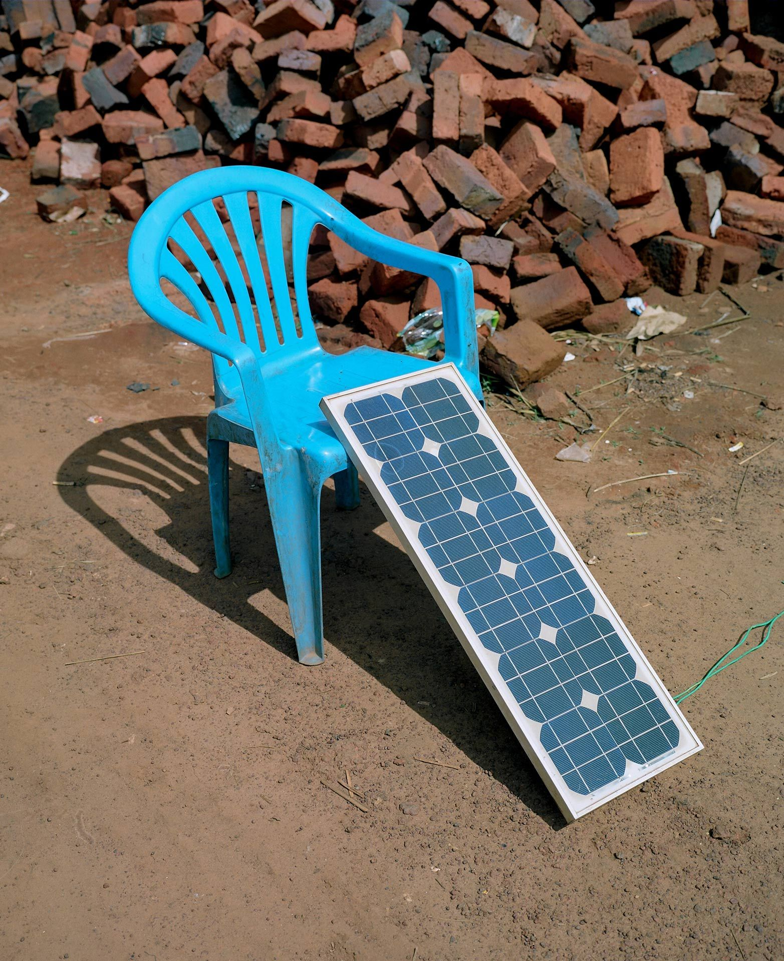 blue plastic chair supporting a transportable solar panel while its recharging by Alexi Hobbs in Uganda for Football for Good with Sportsnet