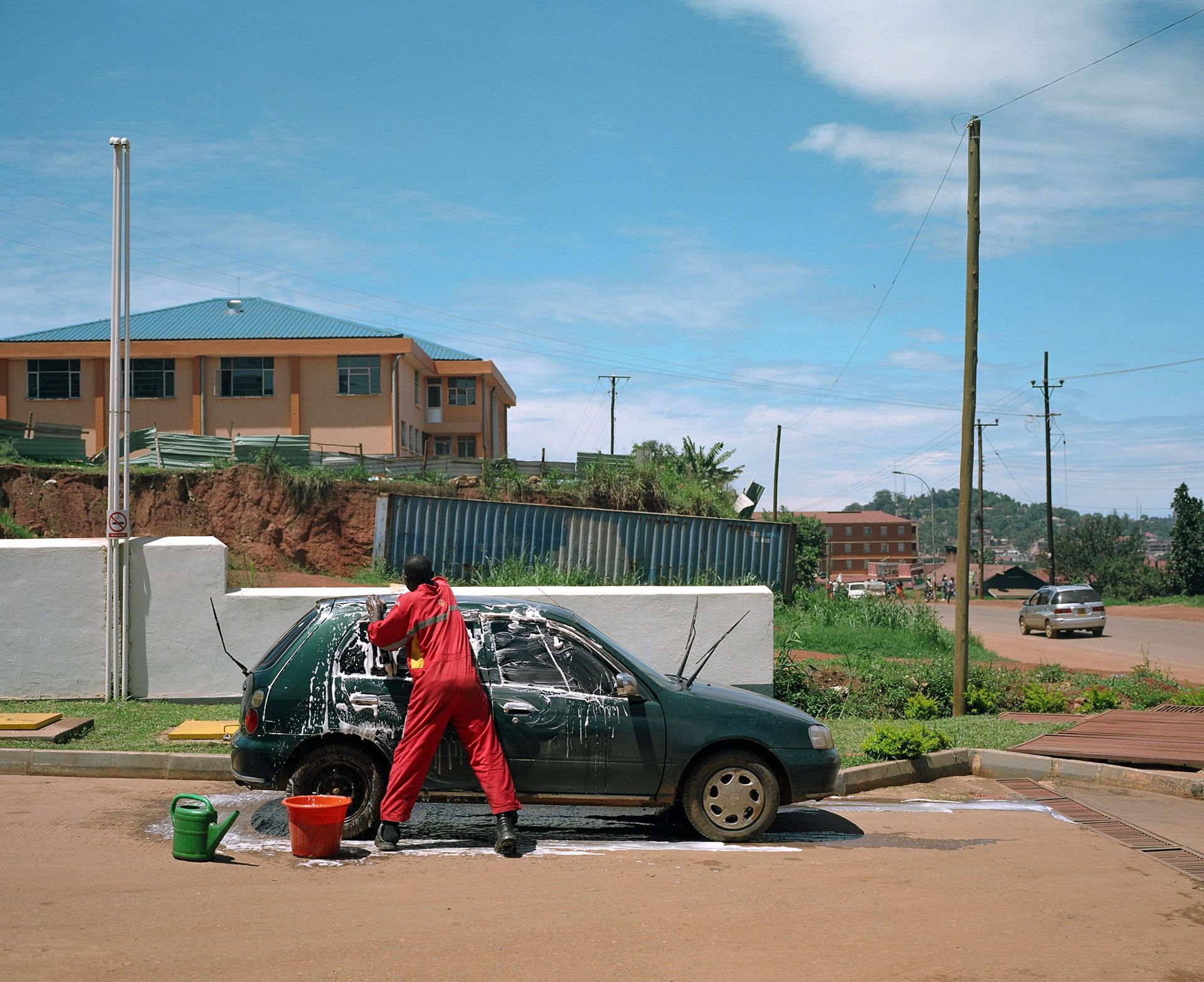 black man all dressed in red washing a dark green car by hand in the sun by Alexi Hobbs in Uganda for Football for Good with Sportsnet