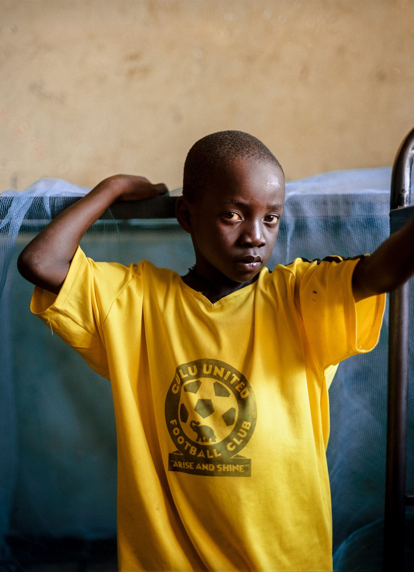 young black boy looking at camera wearing yellow soccer jersey by Alexi Hobbs in Uganda for Football for Good with Sportsnet