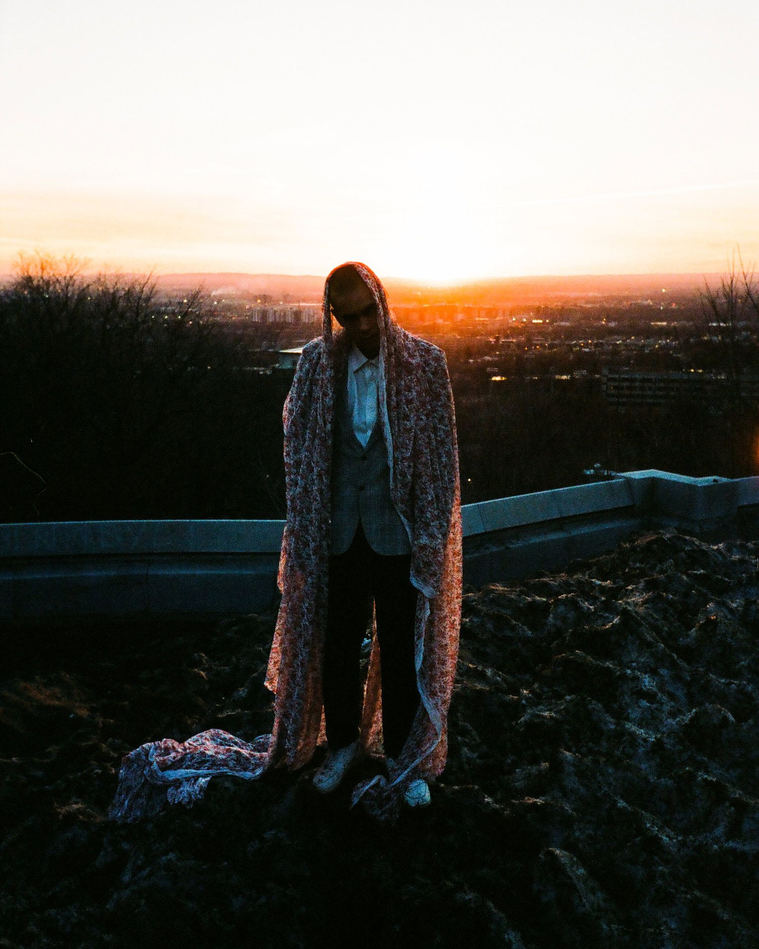 singer Yuki Dreams Again posing on rocks at sunset with flowery colourful piece of lace fabric over his head and shoulders in behind the scenes of their promotional video filmed by Les Gamins