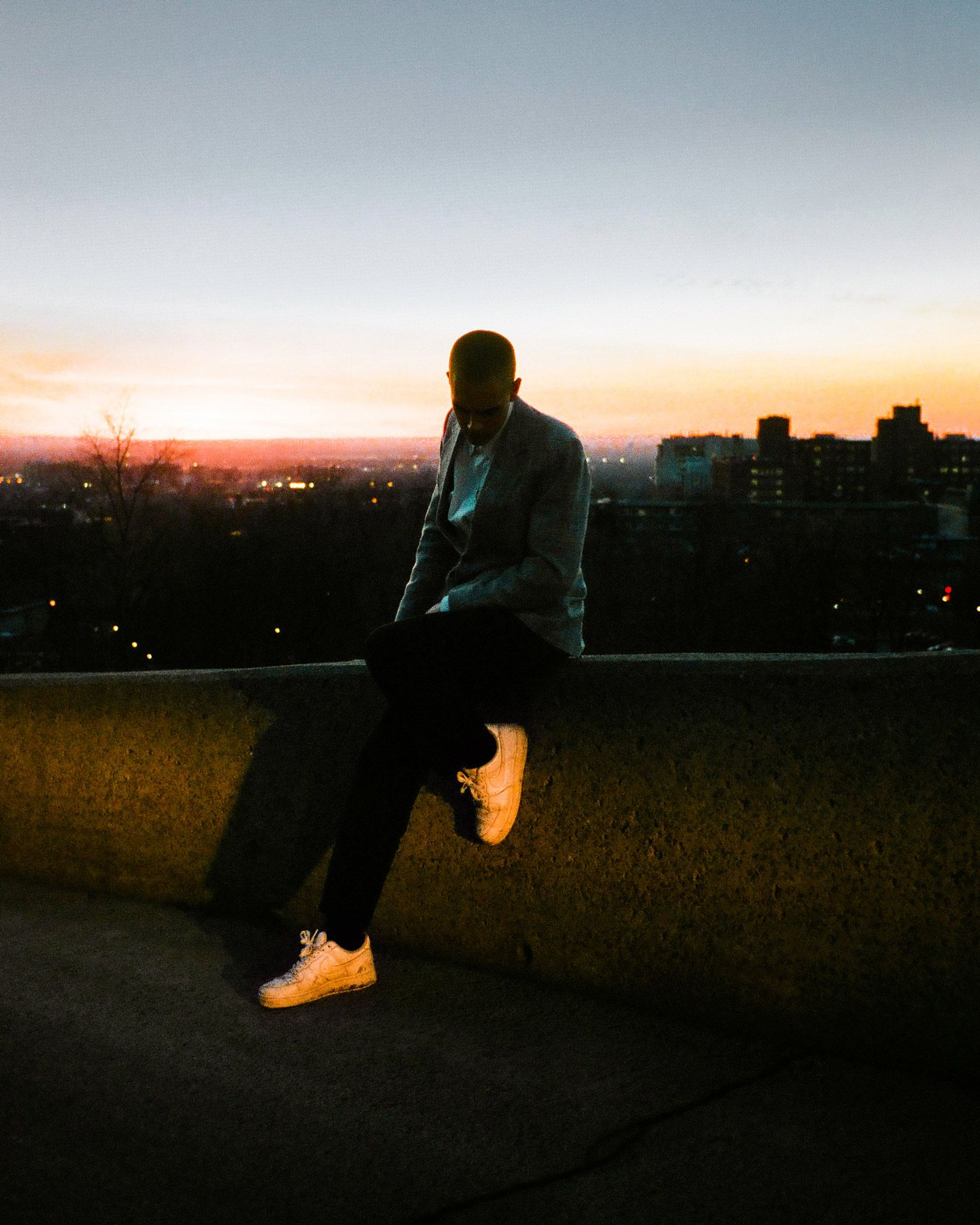singer Yuki Dreams Again sitting on small stone wall at sunset with shoes blasted in orange light in behind the scenes of their promotional video filmed by Les Gamins