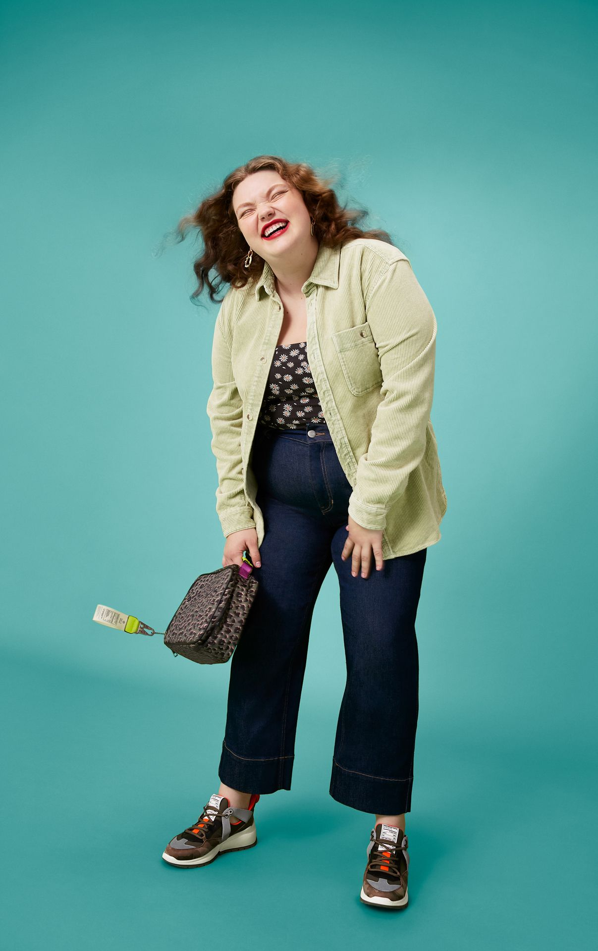 Curvy lady smiling with her hair in the wind. She is in front of a turquoise background and wears blue jeans, green corduroy shirt, Call It Spring shoes and holds a Call It Spring purse.