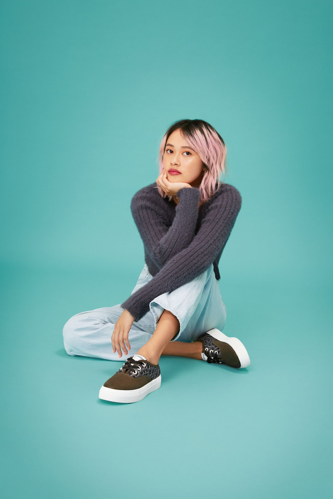 Young woman with pink wavy hair wearing pale blue jeans, Call It Spring sneakers and sitting on a blue turquoise background.