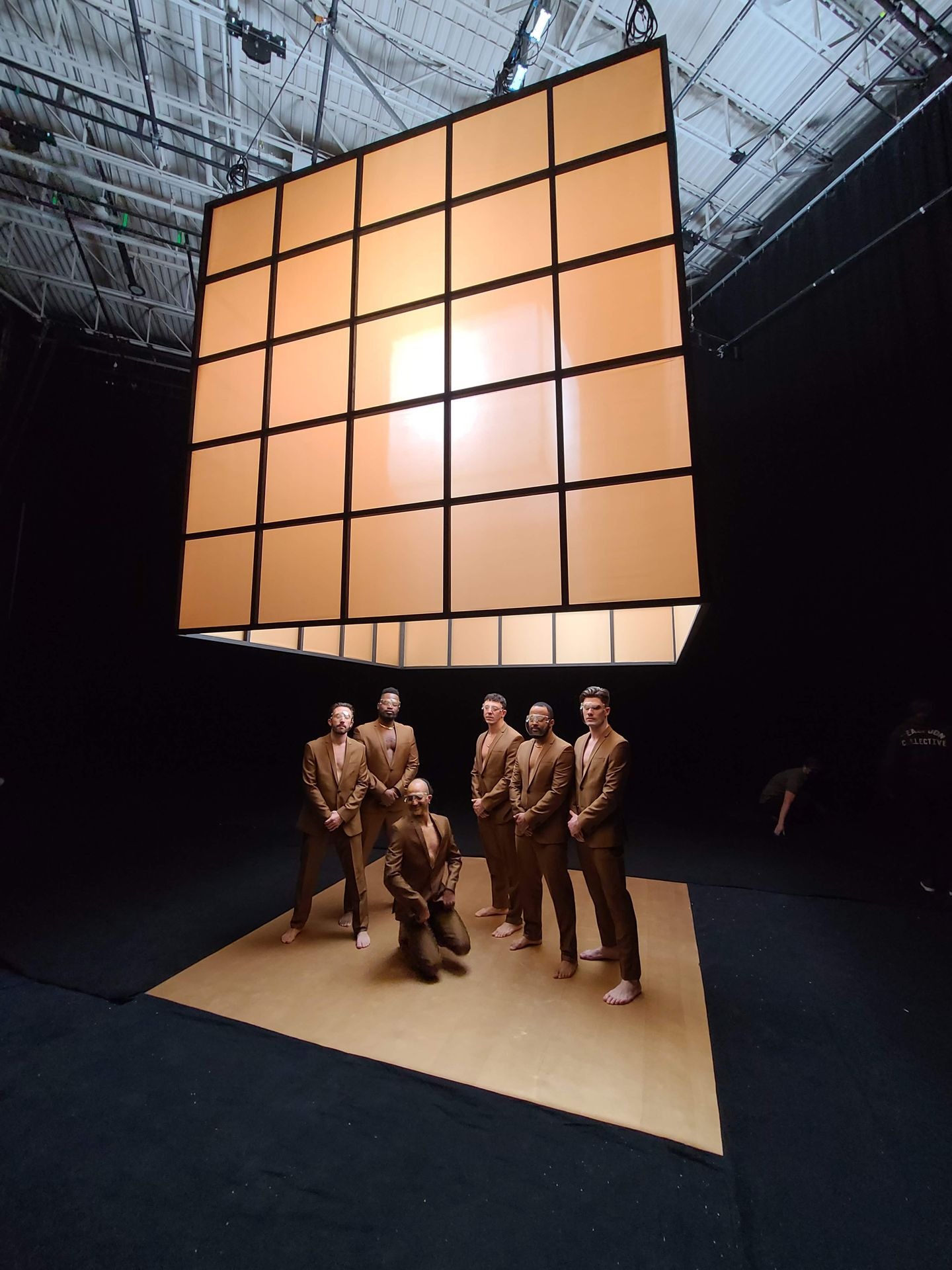 Behind the scenes photo with dancers wearing beige suits posing under a big cube which is lighted in a black studio.
