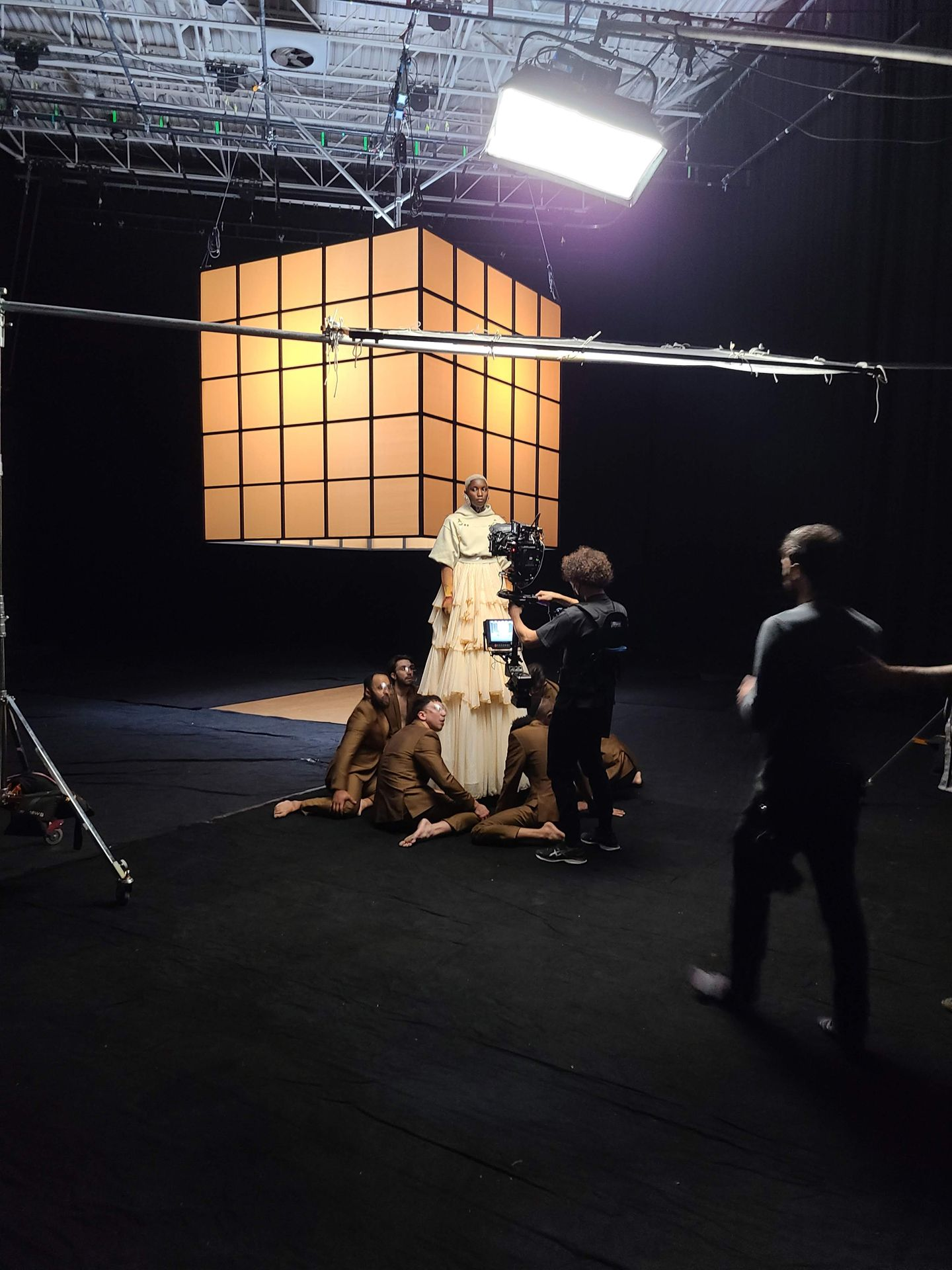 Behind the scenes image in a black studio, the cameraman is filming Sarahmée standing on a pedestal with the dancers sitting around her.
