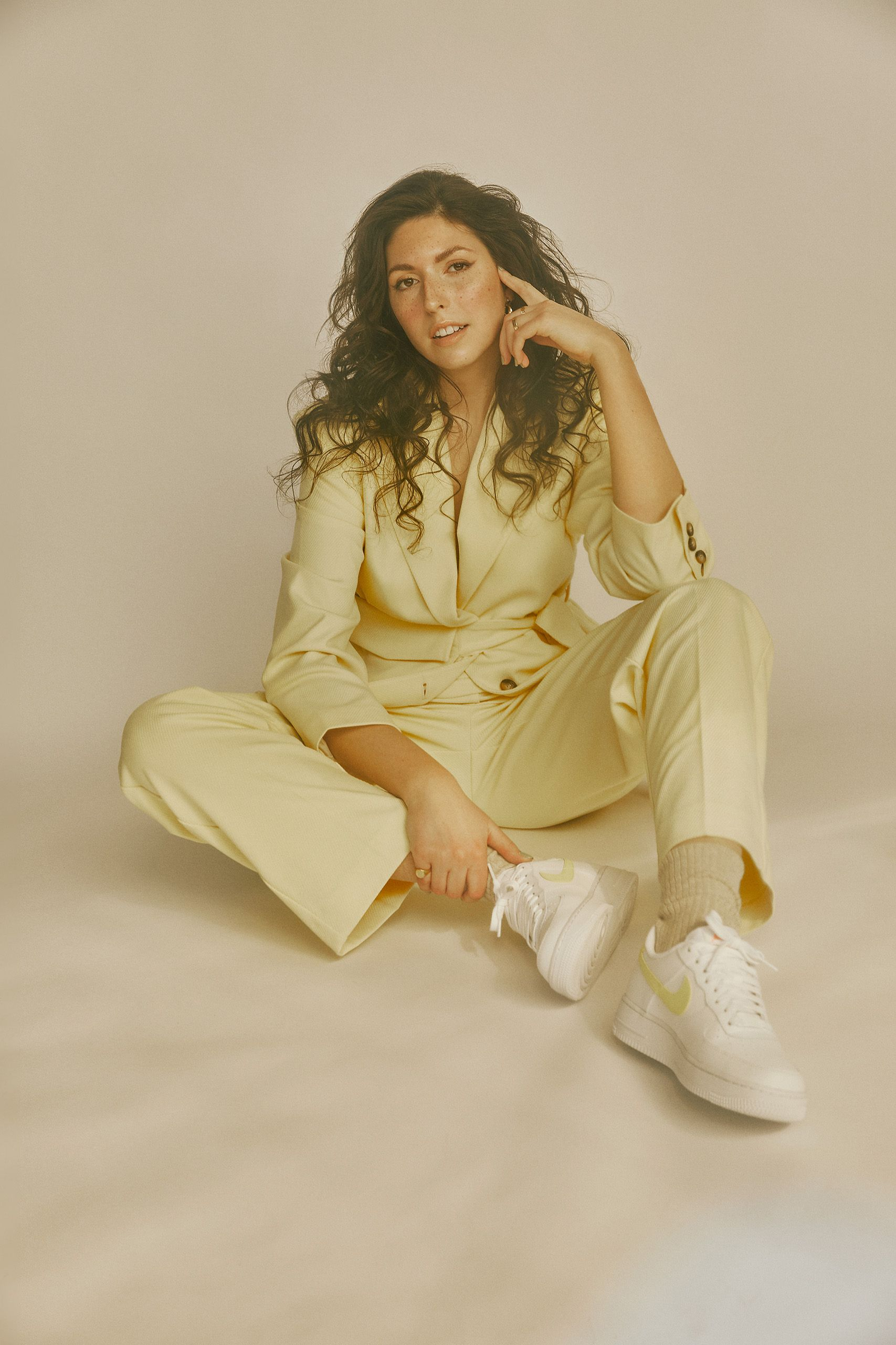 Woman singer songwriter sitting on the ground yellow outfit white backdrop photography Montreal