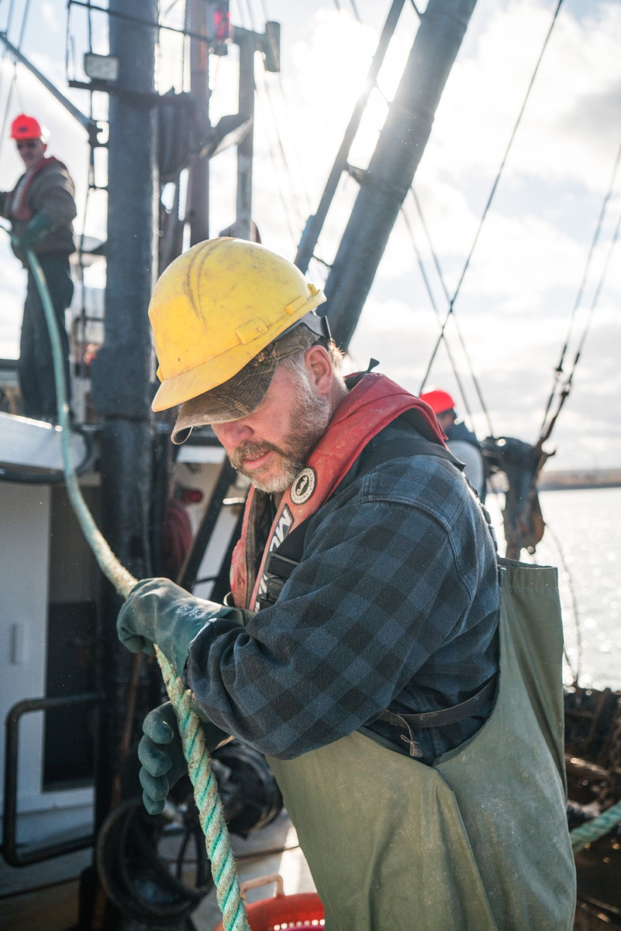 fisherman wearing yellow helmet holding rope by Bruno Florin for Ricardo Magazine in Bay of Fundy