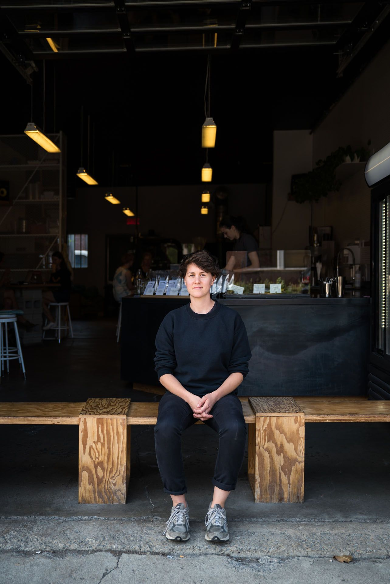 young woman sitting on wood bench before a coffee shop by bruno florin for mile-ex mille vies