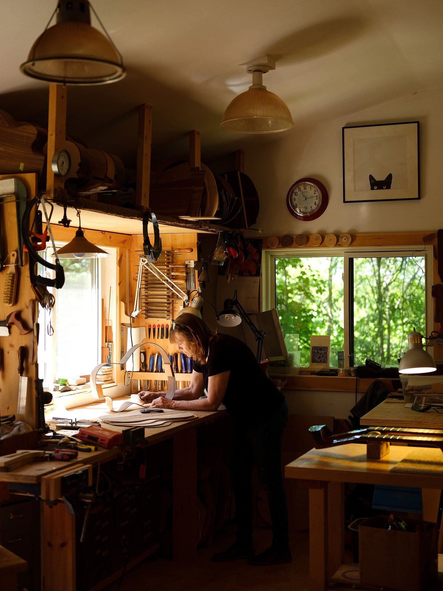 woman in guitar making shop working on model in front of window hunched over table by Guillaume Simoneau for Mercedes Benz Magazine
