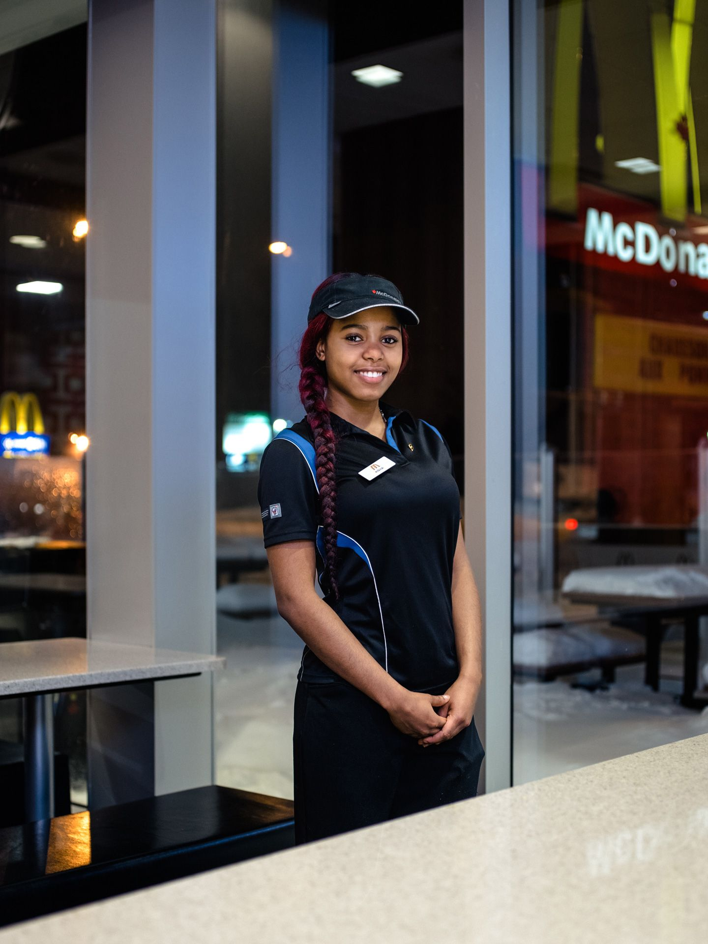 young black female employee smiling at camera by Alexi Hobbs for McDonald's