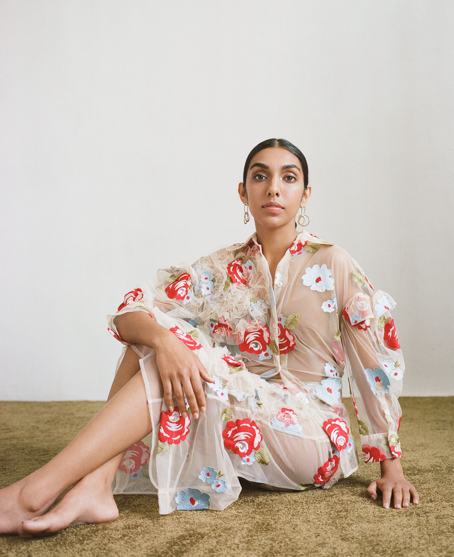 writer Rupi Kaur wearing flower dress looking at camera by Oumayma B Tanfous for Vogue Espana