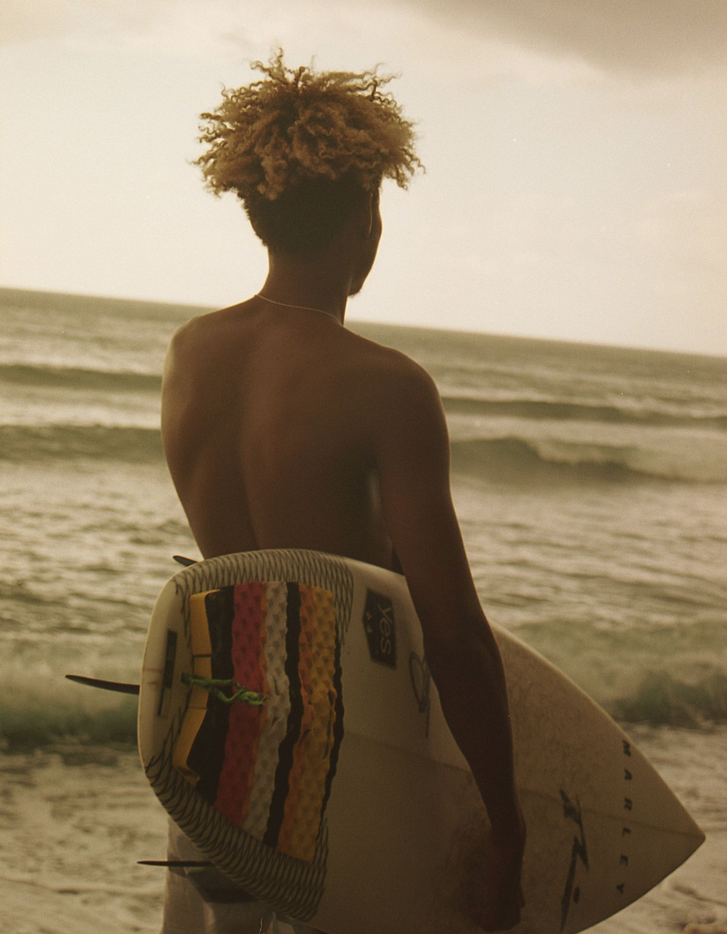 young jamaican man walking toward sea with surfboard under his arm by Oumayma B Tanfous in Jamaica