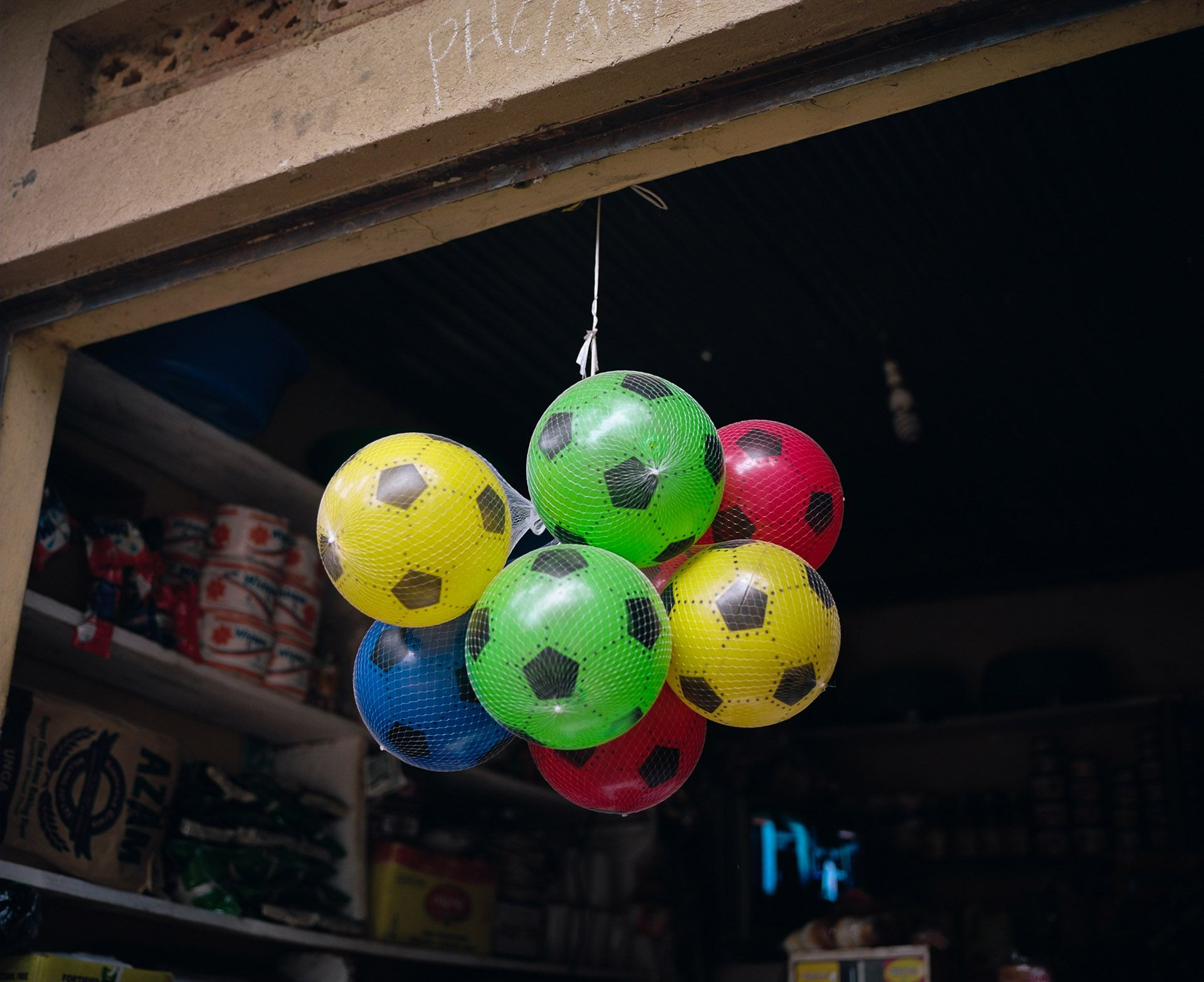 bunch of suspended plastic soccer balls by Alexi Hobbs in Uganda for Football for good with Sportsnet