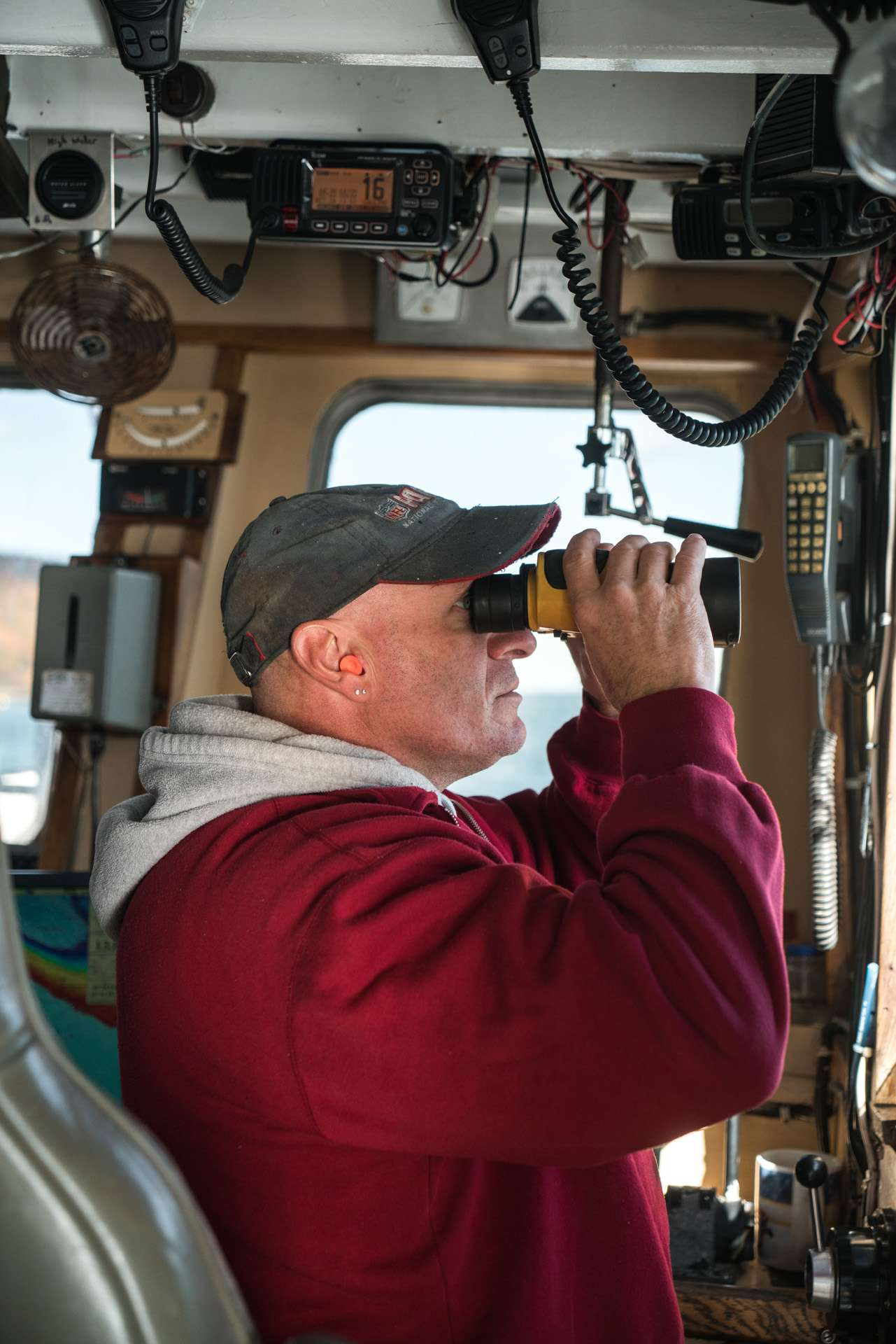 boat captain wearing red jacket looking through binoculars by Bruno Florin for Ricardo Magazine in Bay of Fundy