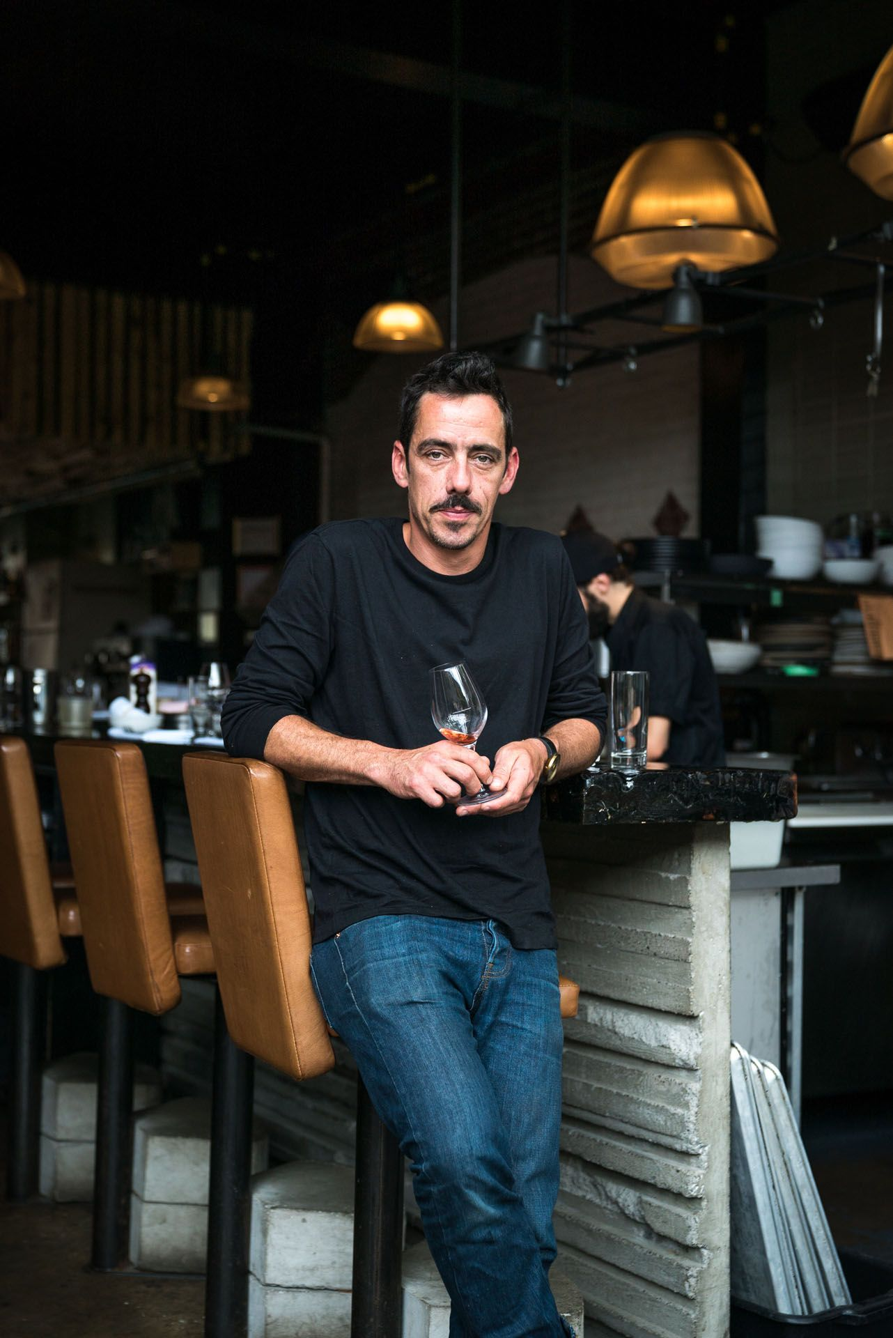 middle aged man standing against bar stool holding almost empty glass of wine by bruno florin for mile-ex mille vies