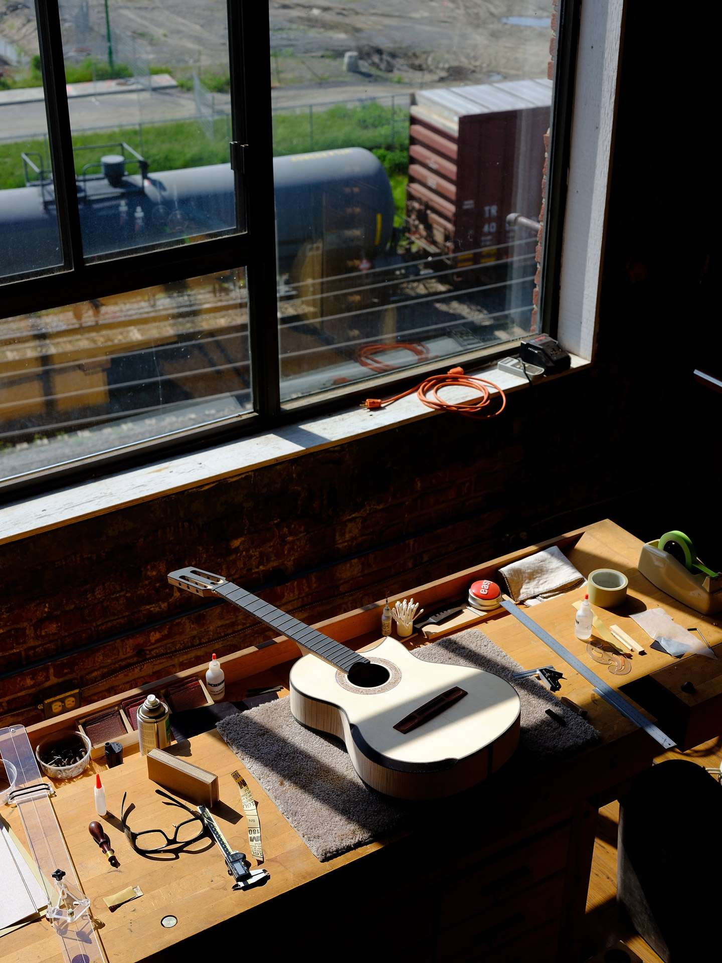 guitar in workshop next to window in the sun by Guillaume Simoneau for Mercedes Benz Magazine