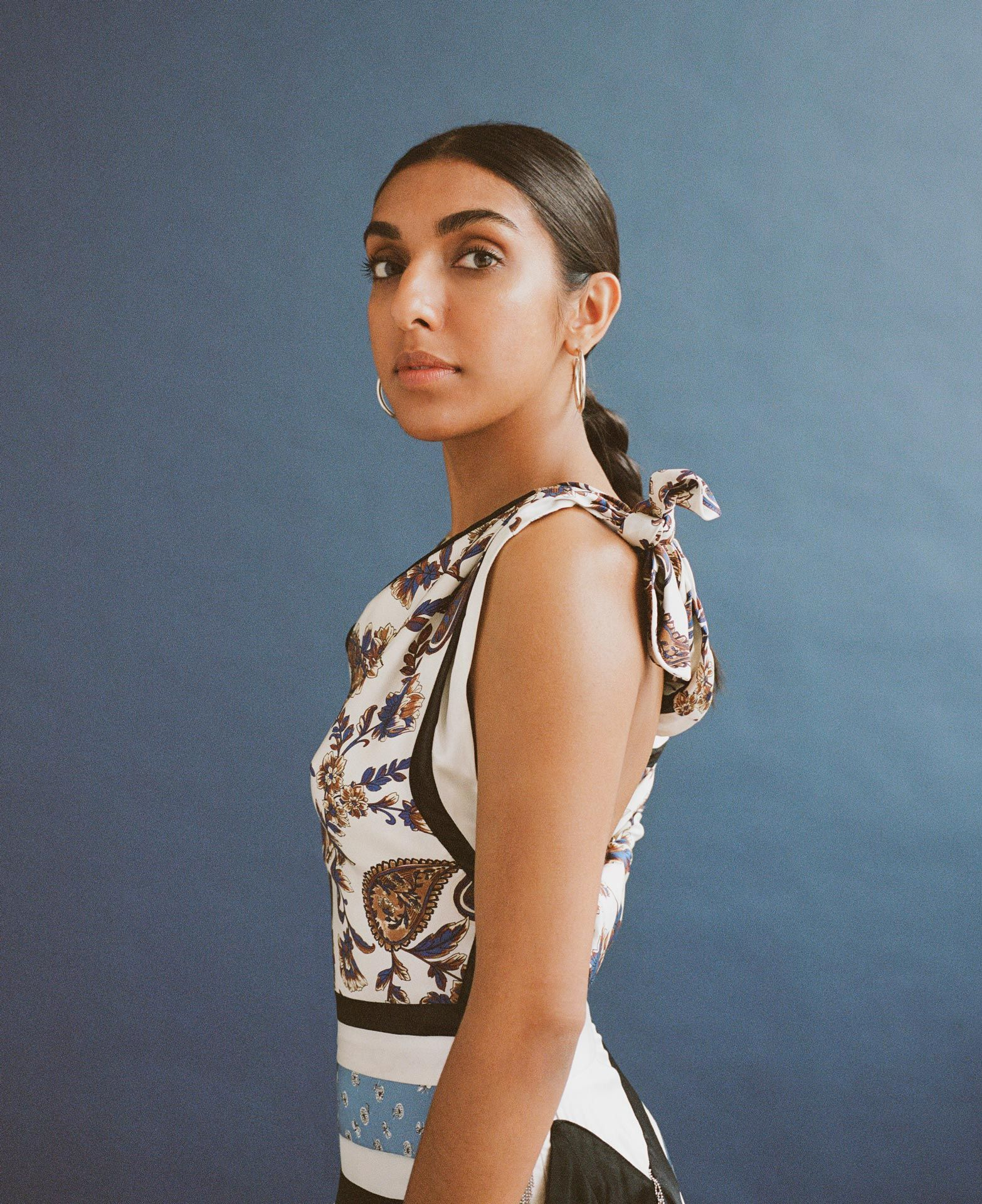writer Rupi Kaur on blue background looking at camera by Oumayma B Tanfous for Vogue Espana
