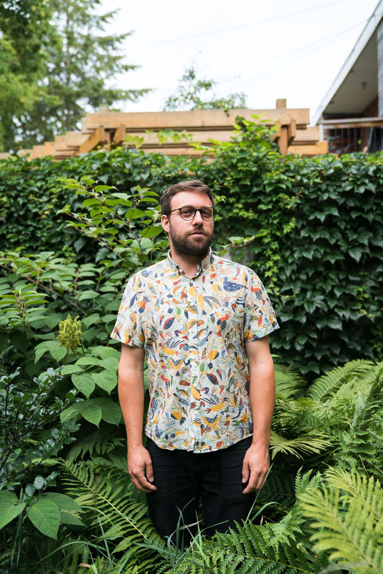 bearded man wearing shirt with colorful birds standing in middle of high plants by bruno florin for mile-ex mille vies