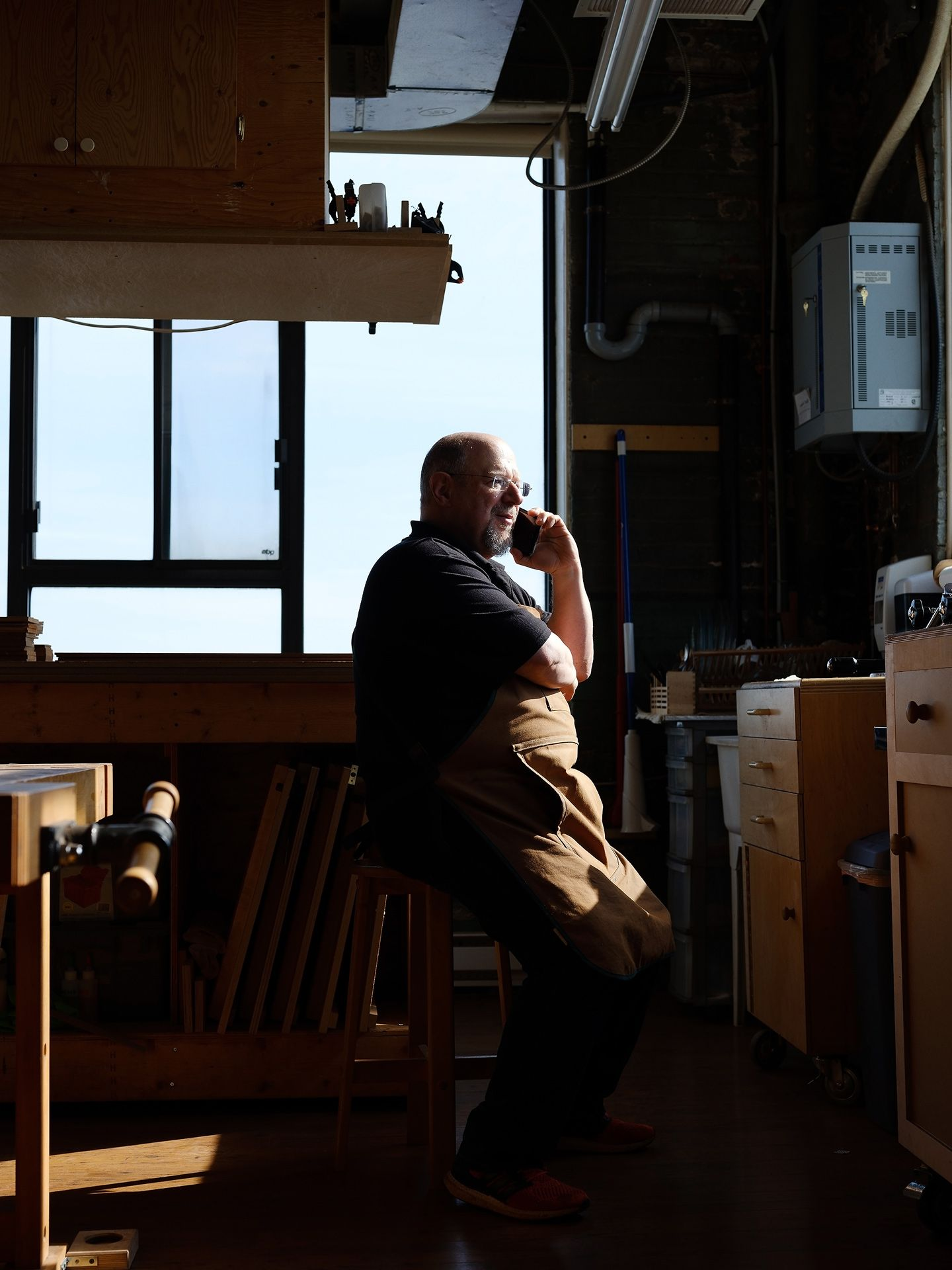 guitar maker sitting on stool in the sun on the phone by Guillaume Simoneau for Mercedes Benz Magazine