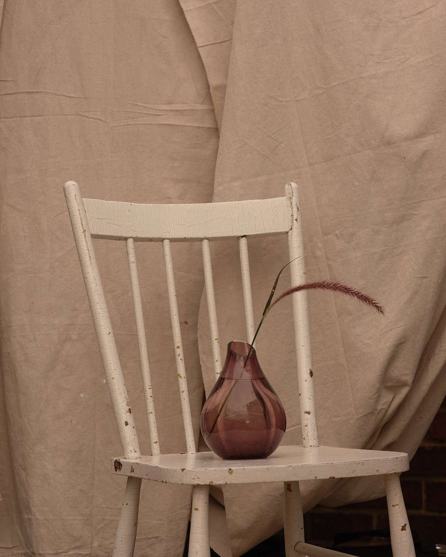 purple vase on white chair with single branch in it by Maxyme G Delisle for Flanelle Magazine