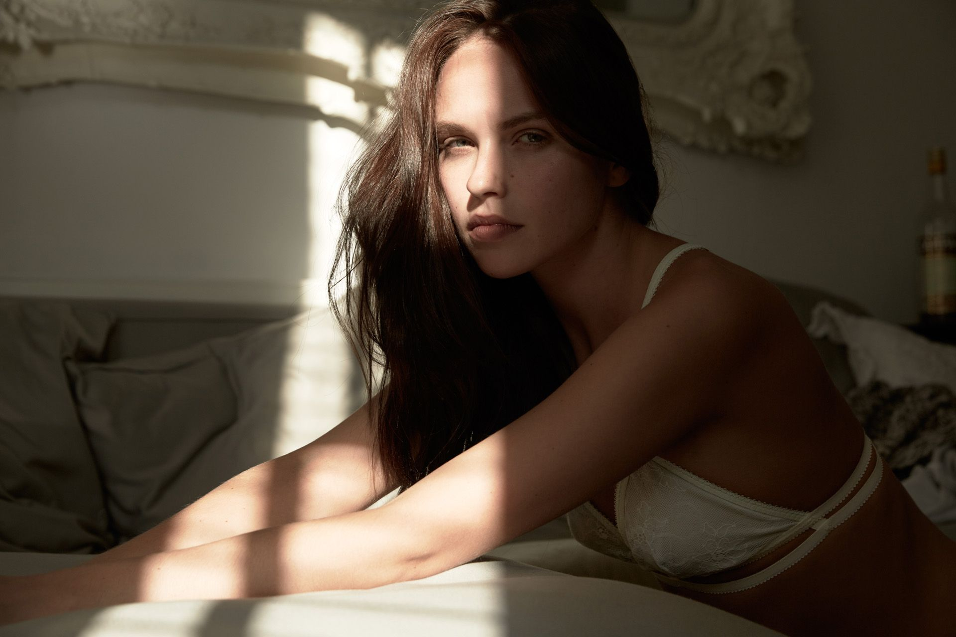 model Kat wearing Iris London lingerie sitting between bed and wall in sunlight by Maxyme G Delisle
